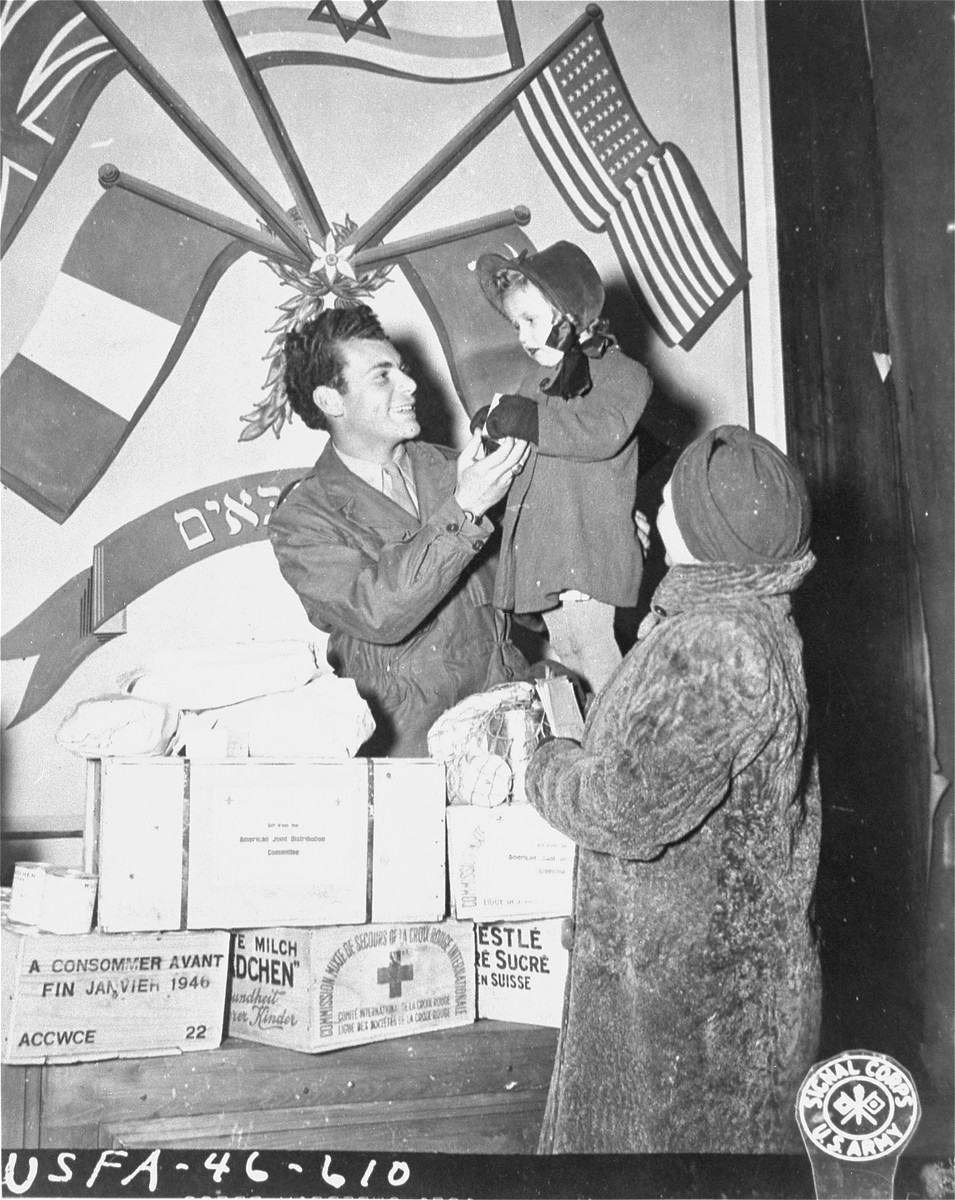 Mrs. Leopold Ruhalter, a Jewish survivor living in Vienna, looks on as her two-year old daughter, Renati, is given a special treat by Harry Weinsaft of the Joint Distribution Committee.  The campaign to distribute food to needy Jewish survivors in Vienna is sponsored by the local Jewish Gemeinde in conjunction with the JDC.