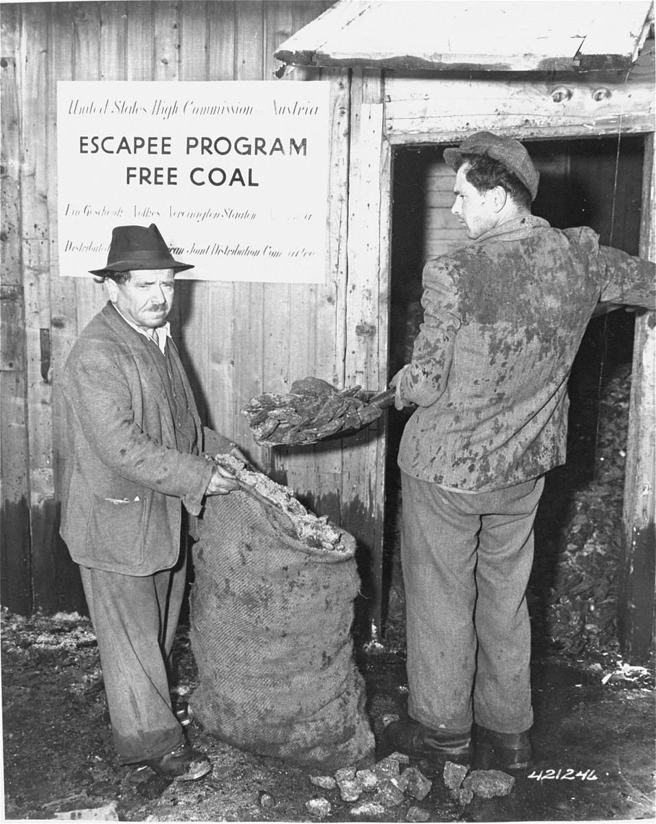 Two displaced persons shovel coal from a free coal repository maintained by the United States High Commision Austria.