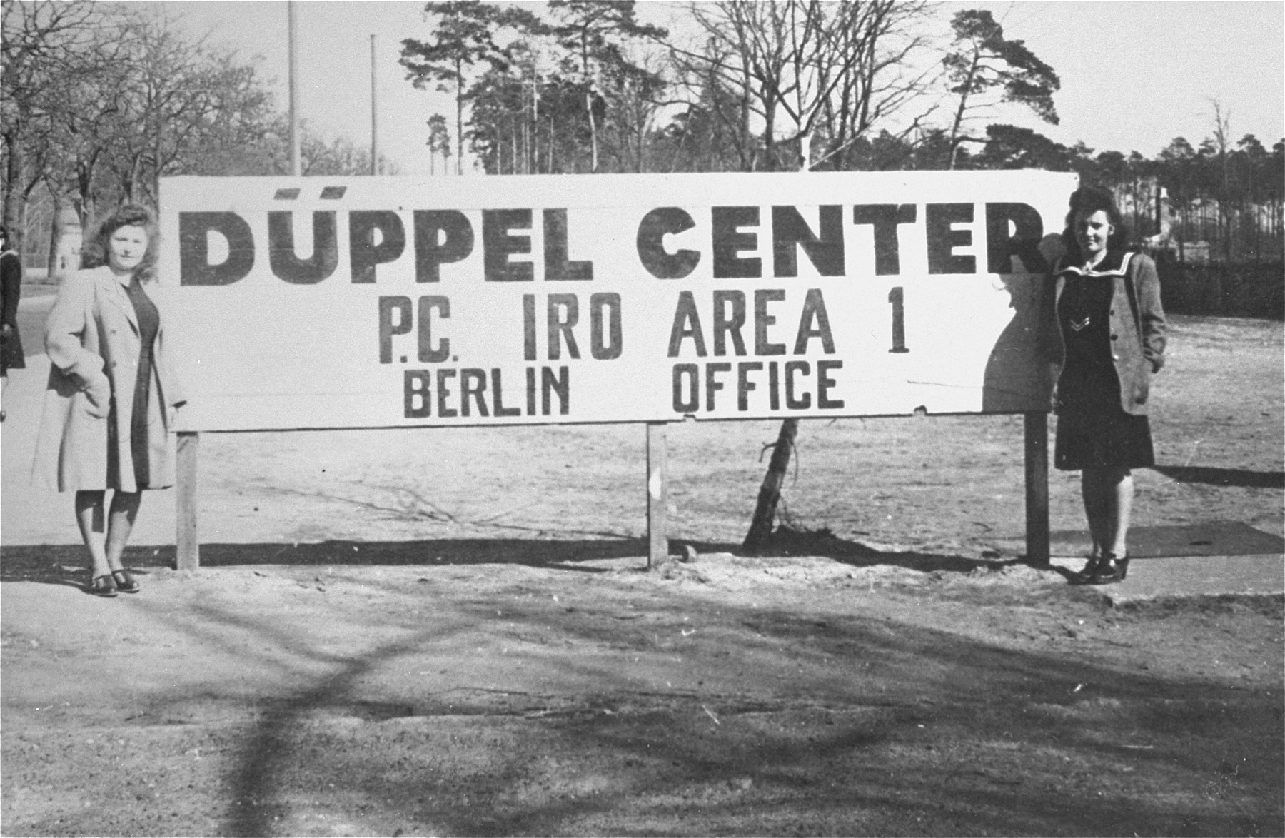 Lusia Gliklich (left) and Andzia Dell stand beside the sign in front of the Schlachtensee displaced persons camp.