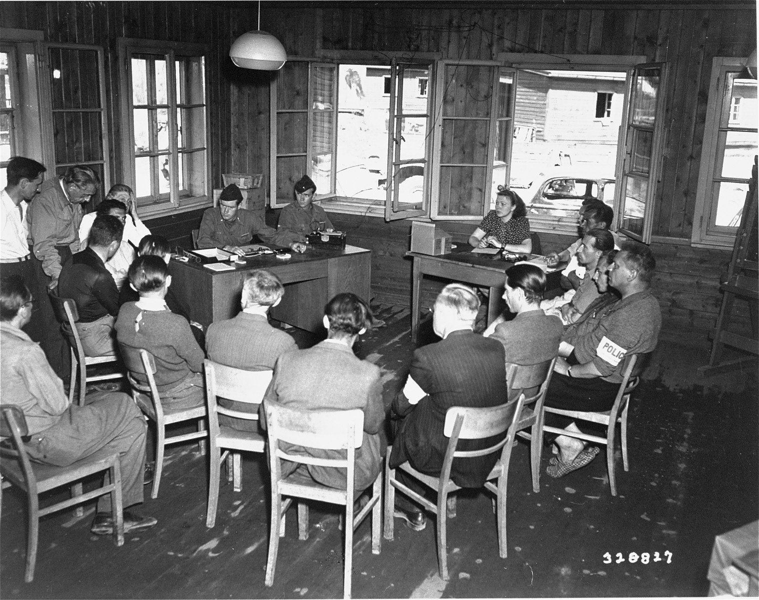 Civilian and military administrative staff of an unidentified DP camp in Austria gather for a daily meeting.   Seated in a semi circle are: 1st Lt Roger W. Perry, Phoenix, Arizona, camp commandant and 1st Lt David B. Moore, Winona, Mass, executive officer.