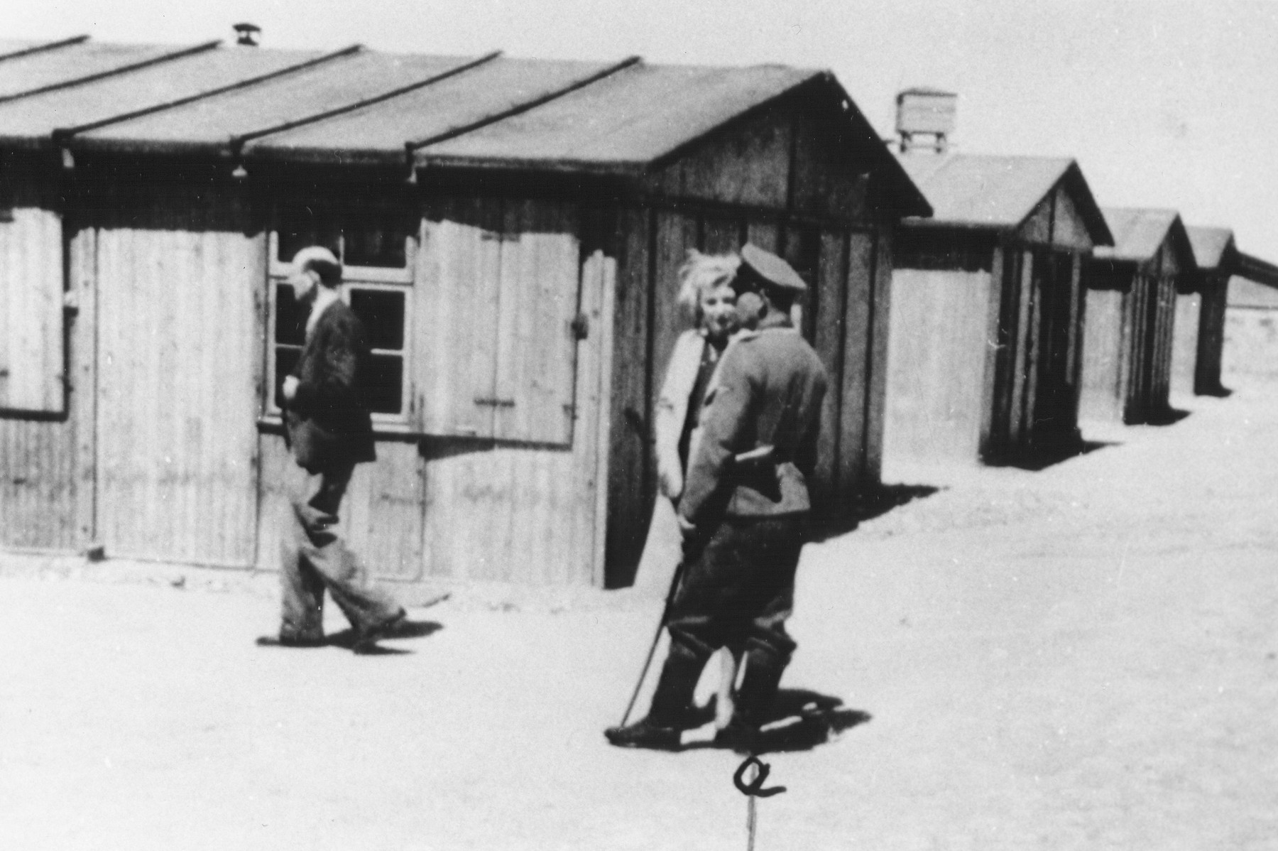 An SS officer identified as Lehnert converses with a woman on the main street of the residential camp in Trawniki.