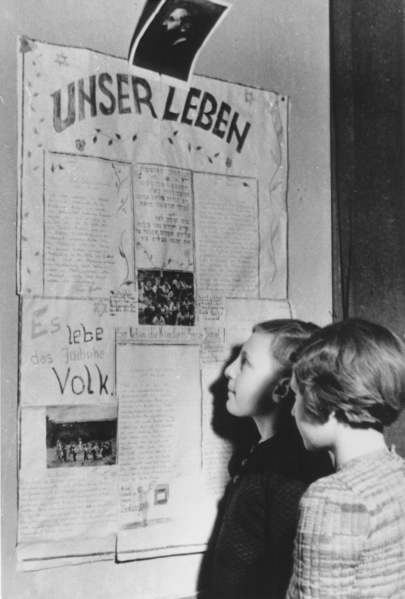 Two Jewish DP children read a newspaper posted on the wall of the Jewish (Deutsche Juedische Jugend) school at the Berlin Chaplains' Center.