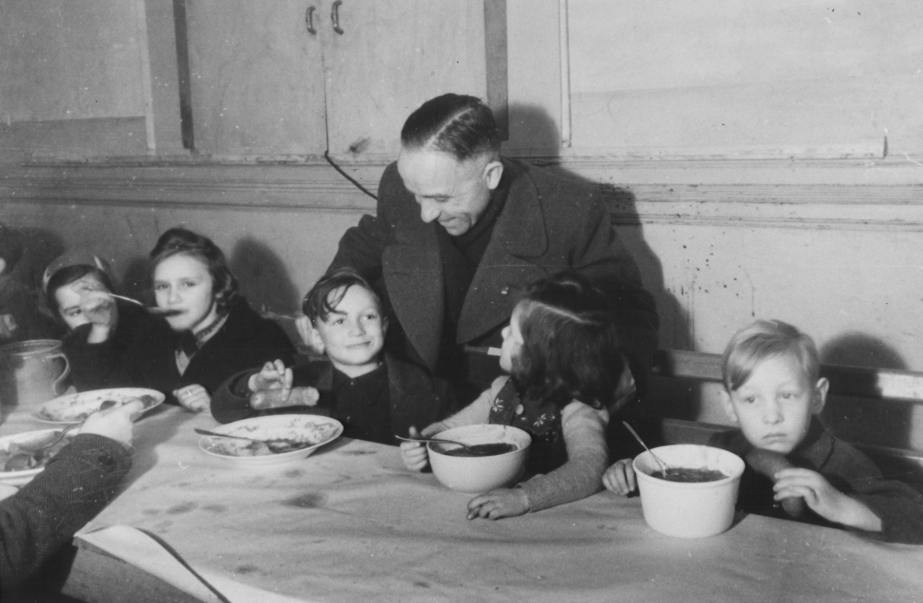 Julius Meyer (standing) meets with DP children eating lunch in in the Jewish (Deutsche Juedische Jugend) school at the Berlin Chaplains' Center.