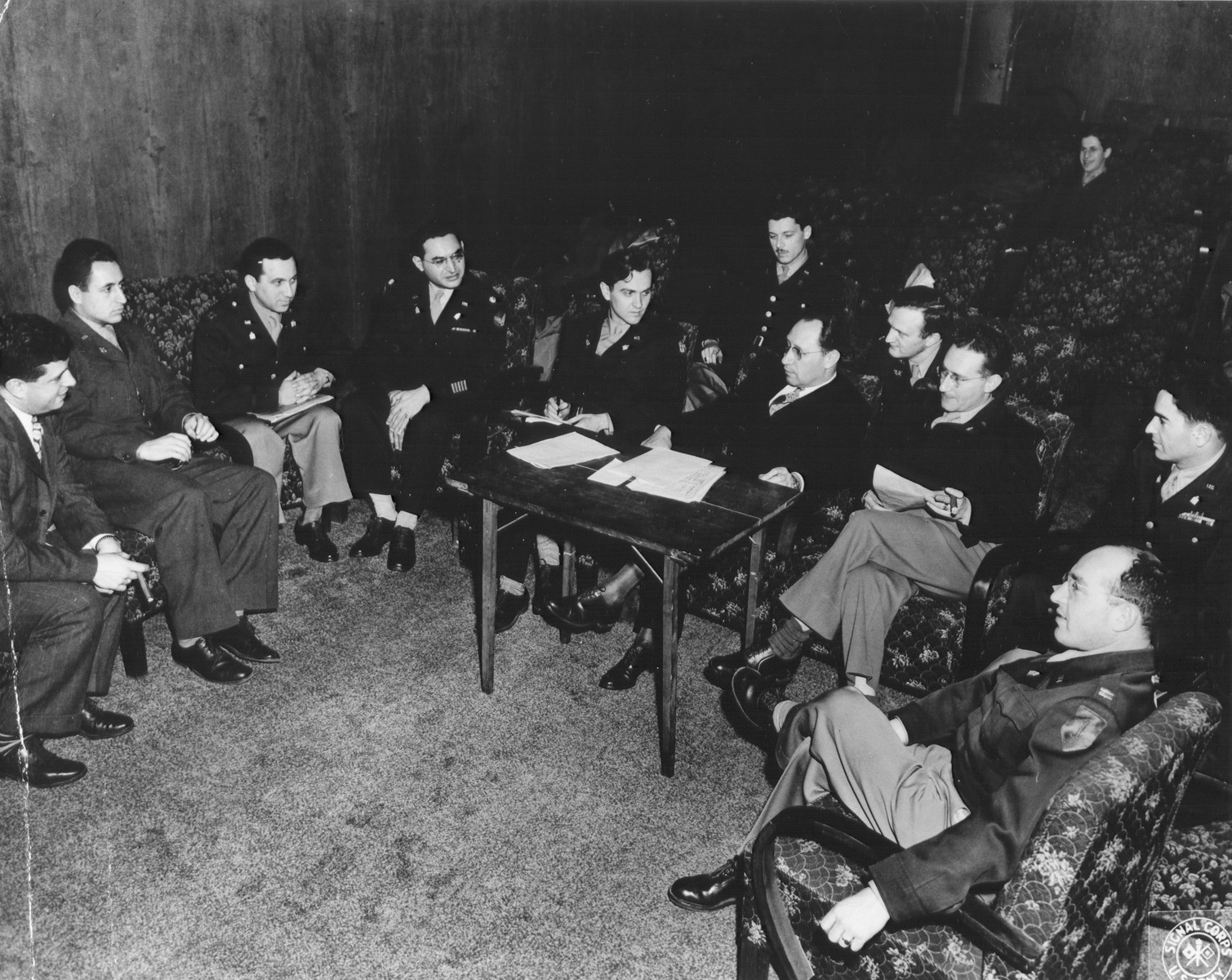 U.S. army chaplains attend a meeting in Frankfurt-am-Main called by Samuel Haber.  Pictured from left to right are: unknown, Samuel Burstein, Salinger (?), Max Brande (?), Mayer Abramowitz, Eliphant, Samuel Haber (sitting at table), Abraham Hyman, Jerry Robbins, unknown, unknown.
