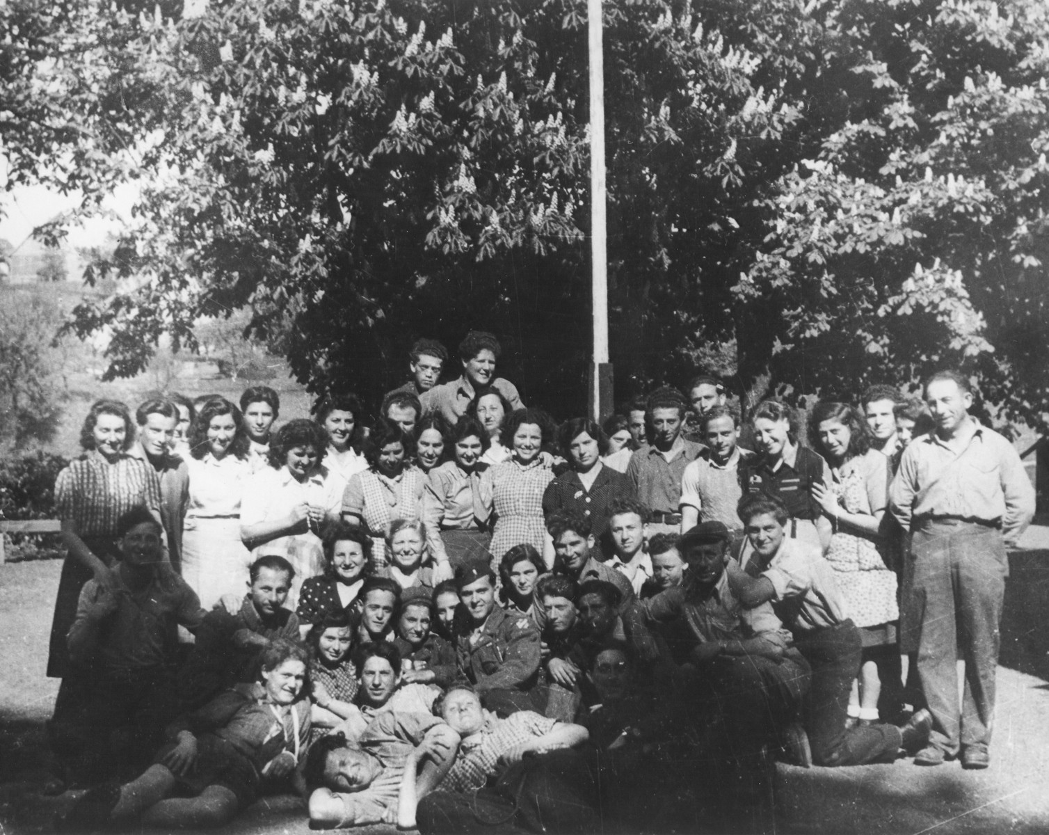 Group portrait of members of Kibbutz Buchenwald.  Mayer Abramowitz is pictured in the center wearing a military uniform.