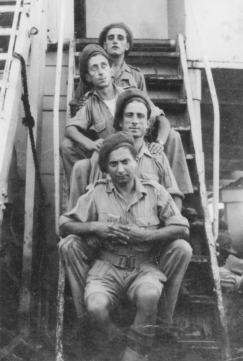 Abba Kovner, disguised as a Jewish Brigade soldier, poses with three others on the steps of the ship that was to take him back to Europe after completing his mission to Palestine on behalf of the Nekama organization.