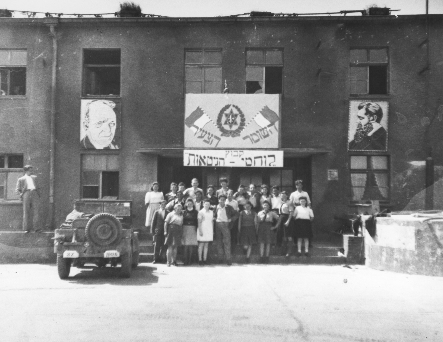 "Members of Kibbutz Lochamei HaGhettaot (Ghetto Fighters) pose outside their headquarters in Berlin beneath two Hebrew banners that read: ""Hashomer Hatzair"" and ""Kibbutz Lochamei HaGhettaot"" and large portraits of Theodor Herzl and Chaim Nachman Bialik."