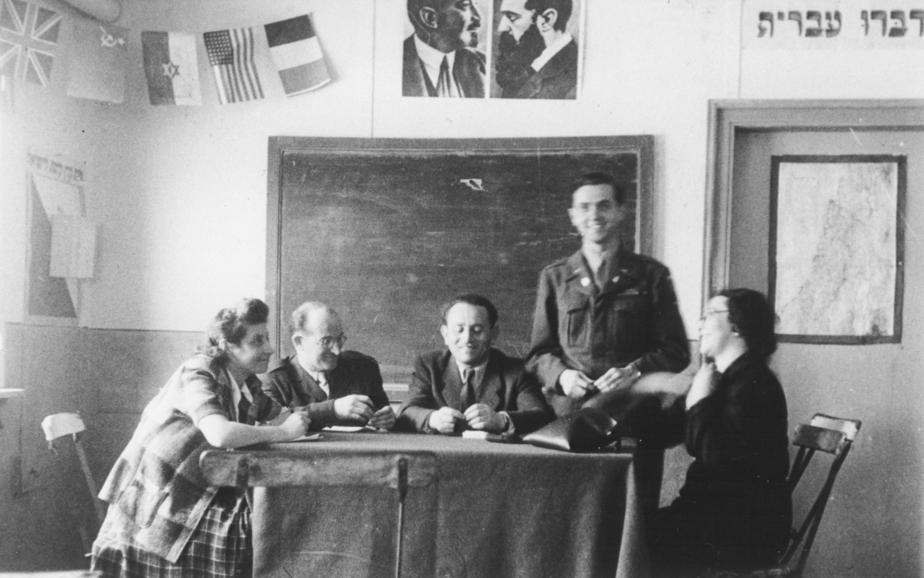 """U.S. Army chaplain Rabbi Mayer Abramowitz meets with teachers of the Hebrew school he established at the Schlachtensee displaced persons camp.  The sign on the wall reads, """"Speak Hebrew."""" Above the blackboard are portraits of Theodor Herzl and Chaim Weitzmann."""
