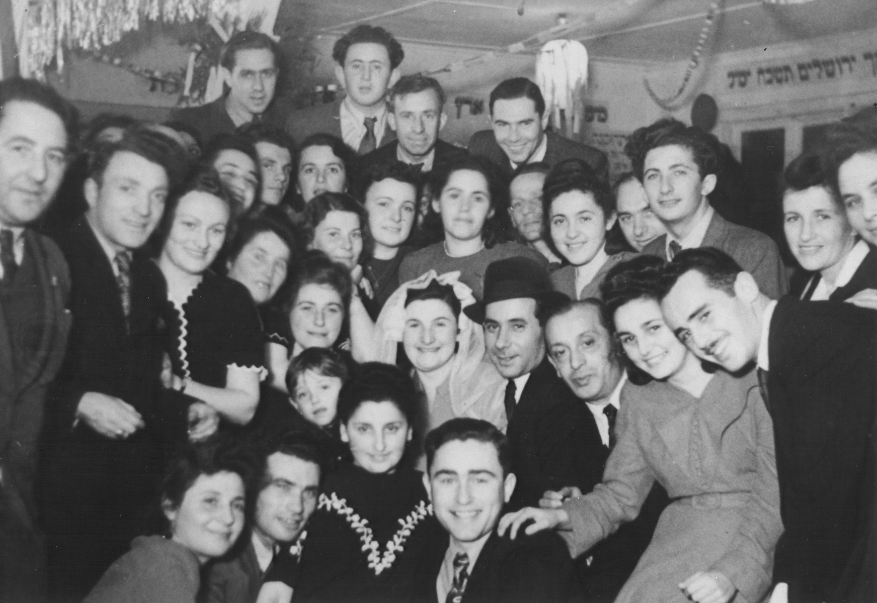 A group of Jewish DPs who are students at a teacher training center in Berlin, pose with one of their instructors and his bride at their wedding in the Schlachtensee displaced persons camp.   The wedding was officiated by Mayer Abramowitz.  Among those pictured are Yitzhak Warszawski, principal of a Jewish school in Wittenau (far left), Tonia Delaticki (standing behind the bride), David Gutensky (front row, center), Rachel Kosowski (second row from the front, second from the right, wearing a belted dress) with belt), Yeshayahu Zycer (top row, center), Leonhard Natkowitz (top row, right) and Michael Gleibermann (third row from the front, third from the right, behind Rachel Kosowksi).