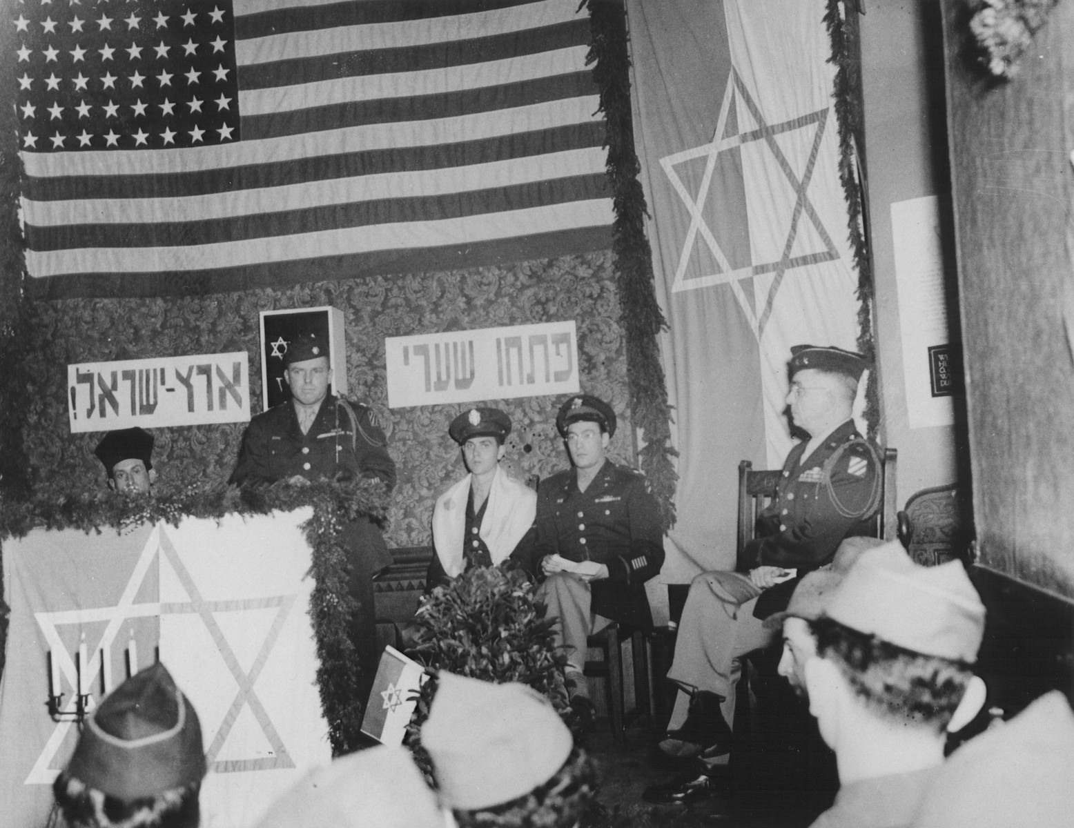 """Major General Frank T. Schmidt (C.G. 3rd Division) delivers a speech at the rededication of a synagogue in Marburg.     The previous synagogue was destroyed during Kristallnacht.  Also pictured is U.S. Army chaplain, Rabbi Mayer Abramowitz (third from the left).  The Hebrew banner reads, """"Open the gates of the Land of Israel."""""""