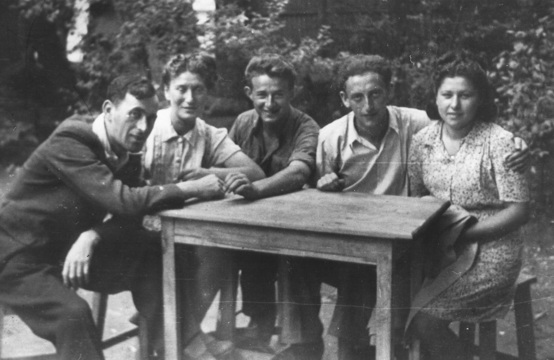 Members of the Nekama group gathered around a table during their stay in Bucharest.  Among those pictured are Baruch Goldstein (left) and Welvel Rabinovich (second from the right).