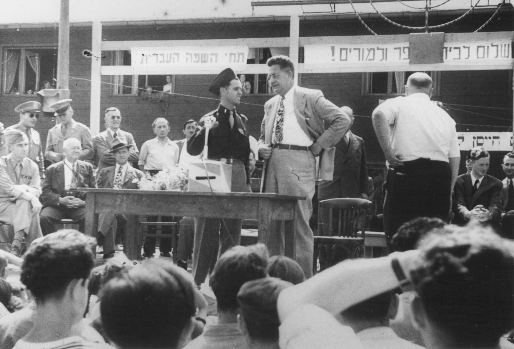 "U.S. Army chaplain Rabbi Mayer Abramowitz converses with an official at an outdoor forum in the Schlachtensee displaced persons camp.  The forum was held for the benefit of a visiting international commission.  Above the podium is a sign in Hebrew that reads, ""Long live the Hebrew language."""