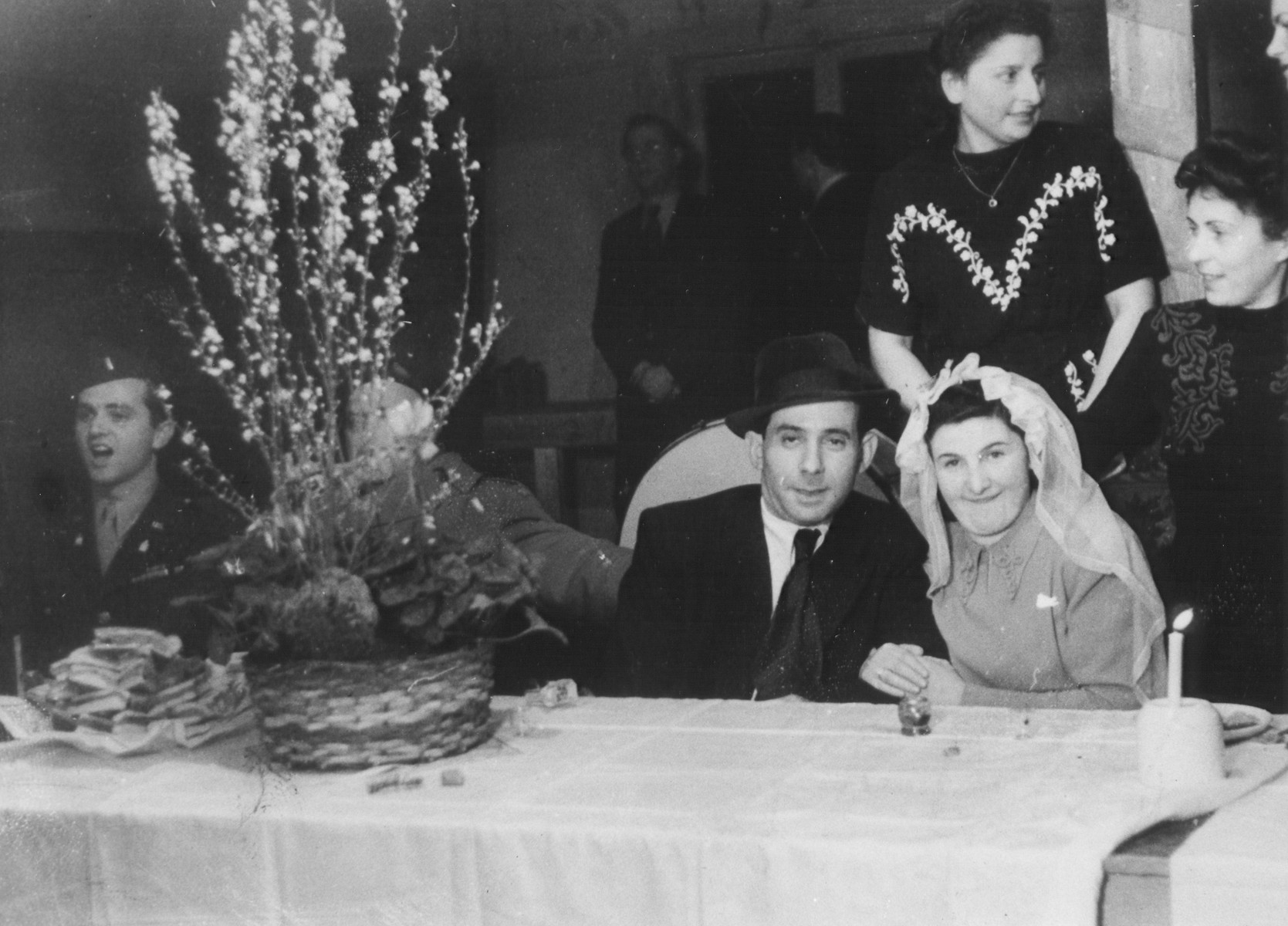 A DP couple celebrates their marriage in the Schlachtensee displaced persons camp.    Pictured on the far left is U.S. Army chaplain Rabbi Mayer Abramowitz.