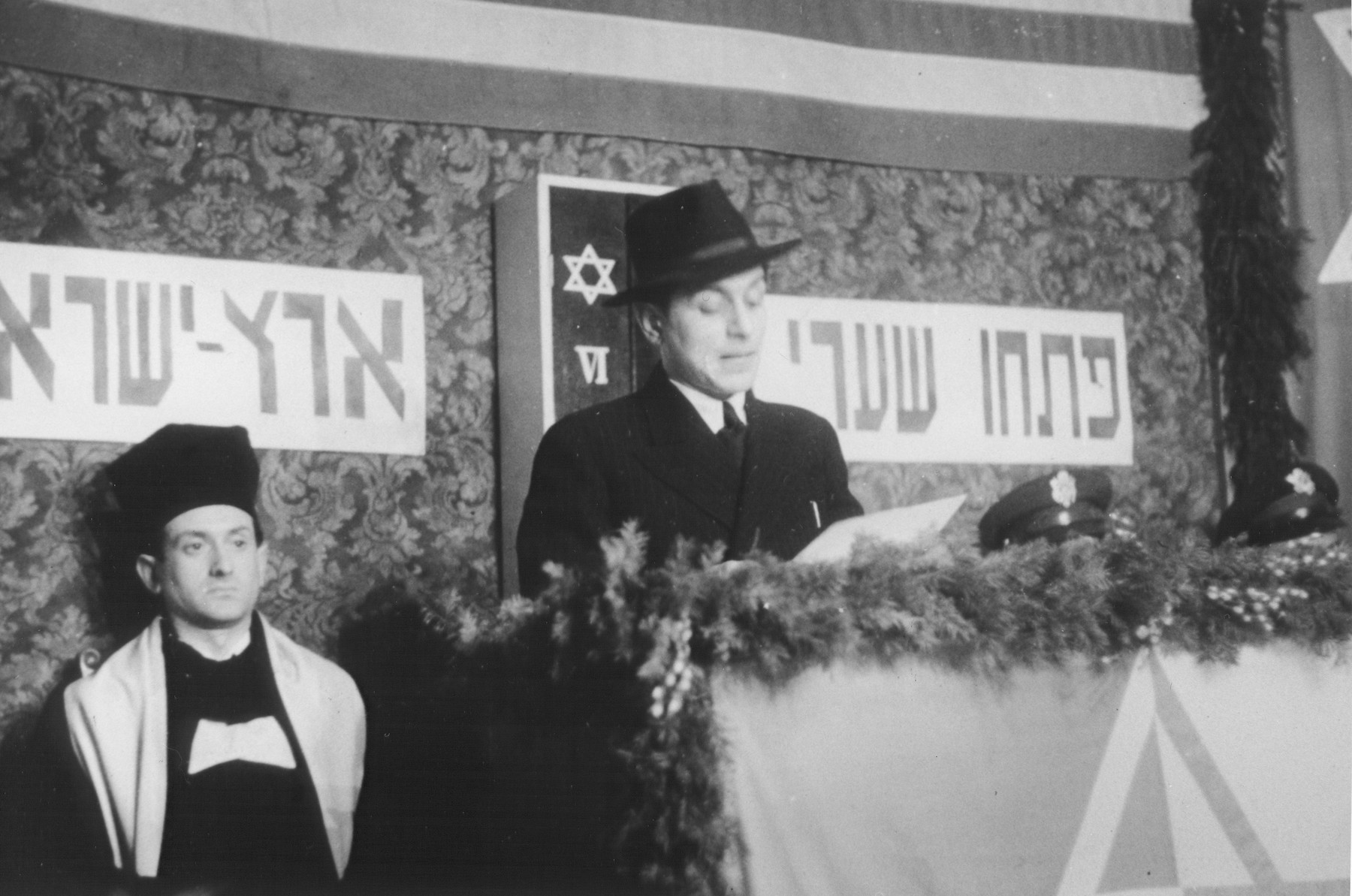"A Jewish DP delivers a speech at the rededication of a synagogue in Marburg.   The previous synagogue was destroyed during Kristallnacht. The Hebrew banner reads, ""Open the gates to the Land of Israel."""