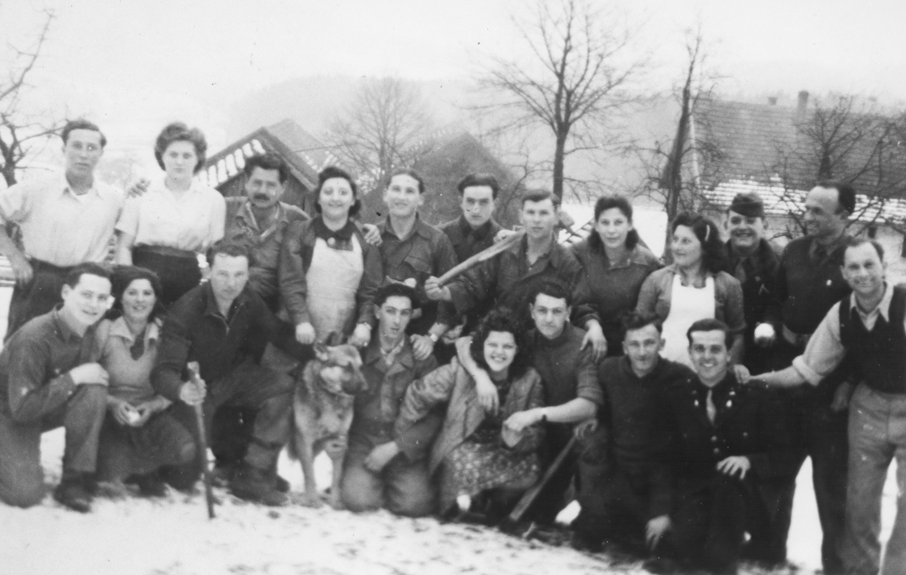Group portrait of members of Kibbutz Buchenwald posing in the snow.  Among those pictured is Mayer Abramowitz (front row kneeling, far right).