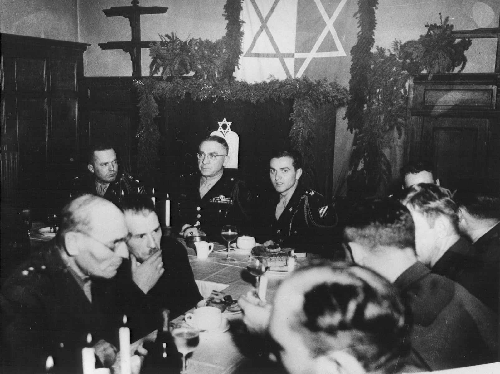 Major General Frank T. Schmidt (C.G. 3rd Division) and U.S. Army chaplain Rabbi Mayer Abramowitz attend a reception during the rededication of the Marburg synagogue.    The previous synagogue was destroyed during Kristallnacht.  Major General Frank T. Schmidt (back table, center), and Mayer Abramowitz (back table, third from the left).