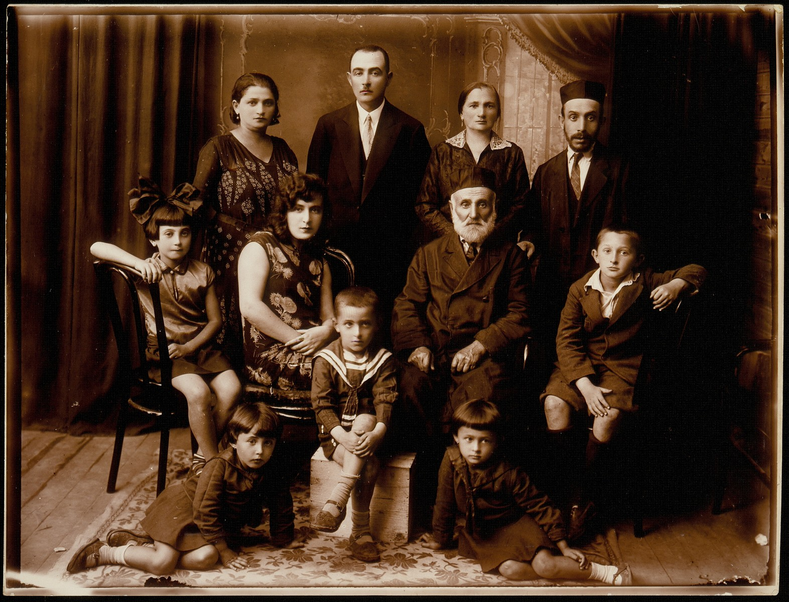 Studio portrait of the extended Zlotnik family in Eisiskes.  The photograph was taken on the occasion of the departure of Dora Zlotnik for Palestine.  Pictured in the back row from right to left are: Yitzhak and Hayya Fradl (Zlotnik) Broide, and Honeh and Bluma (Zlotnik) Michalowski. Seated in the middle row from right to left are: Yankele Sheshko, Reb Shlomo Zlotnik, Dora Zlotnik and Sarah Michalowski.  Seated in the front row from right to left are: ? Sheshko, Moshe Sheshko and Zelda-Bluma Michalowski.  Most of the family was killed by the Germans during the September 1941 mass shooting action in Eisiskes.