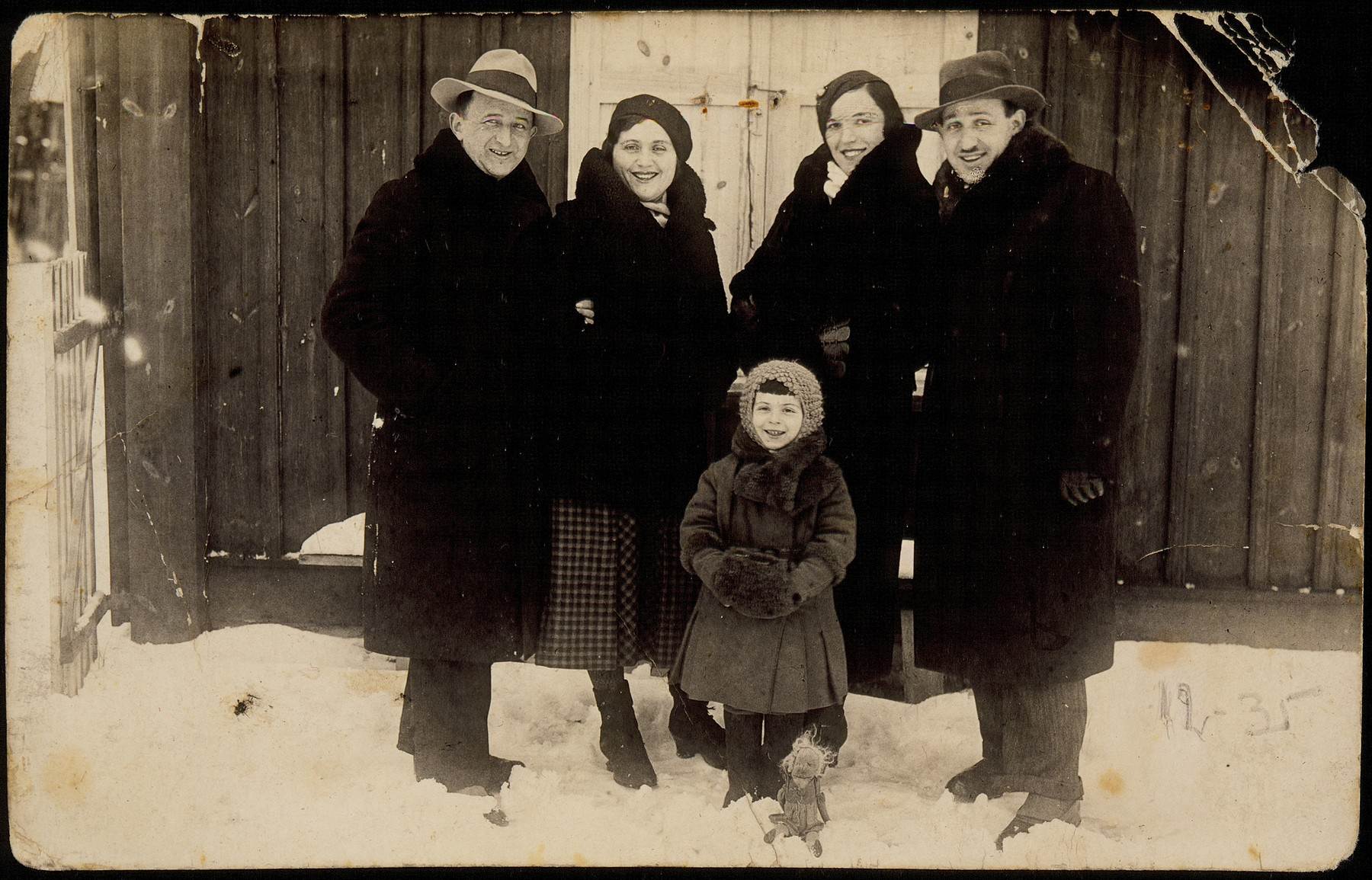 Members of the Sonenson family stand in the snow by a wooden wall.   Standing on the left: Shalom Sonenson Ben-Shemesh and his wife Miriam.  On the right: Miriam's relatives the Bergmans.  The little girl is Gittele Sonenson, the oldest daughter of Shalom and Miriam.  The Bergmans immigrated to Cuba.  Miriam Sonenson was murdered in the Radun ghetto.  Gittele died of TB while hiding in a cave on the Korkus farm a few days before liberation.  Shalom Sonenson (Ben-Shemesh) survived the Holocaust hiding in various locations.