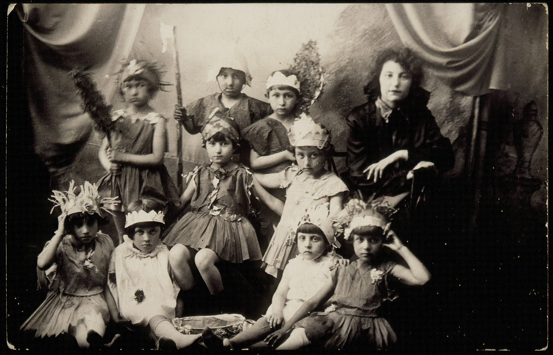 Jewish kindergarten teacher, Rachel Kaleko, poses with her pupils, who are dressed in costumes for a Purim play.  Rachel Kaleko founded the Gani Hebrew kindergarten in Eisiskes.  She immigrated to Palestine in the early 1930s.