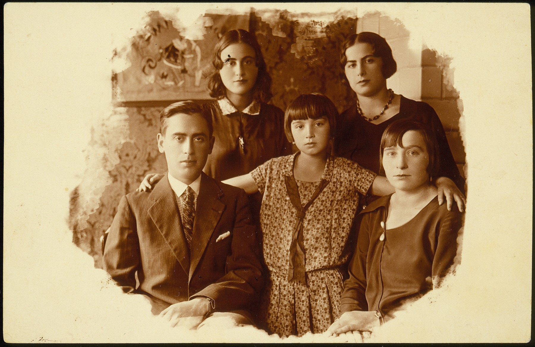 Portrait of members of the Kudlanski and Dubrowicz families in Eisiskes.  Pictured in the front row from right to left is: Hanneh-Beile (Moszczenik) Kudlanski, her daughter Atare Kudlanski  and her cousin Shaul Hayyim Dubrowicz.  Standing behind from right to left are Shaul's sisters,  Leah and Chava Dubrowicz. This photo was mailed by Hanneh-Beile to her two sisters, Sarah Moszczenik and Fradl (Moszczenik) Yrukanski.  Hanneh-Beile and her daughter Atara immigrated to the United States before the war.  The Dubrowicz siblings and their families perished during the Holocaust.
