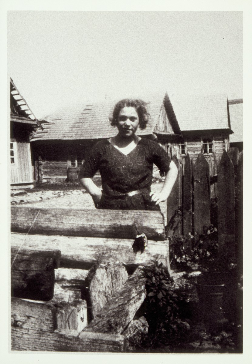 A woman stands by a pile of wood in a yard in Eisiskes.