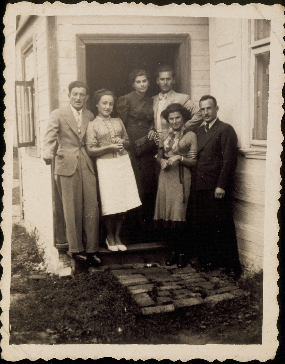 A group of friends poses on the steps of the Sonenson house.  Those pictured include Shepske (Shabtai) Sonenson (left) and Krienele Kanichowski.   All those pictured in the photo were murdered during the Holocaust.