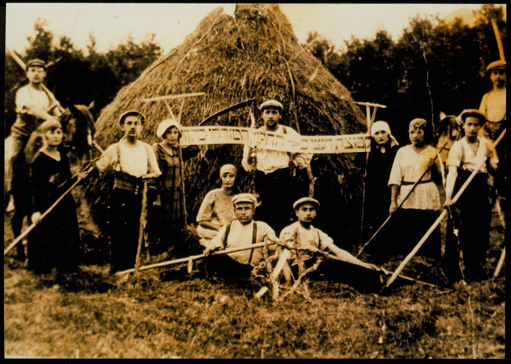 "Members of the Neziv group of the Hehalutz Hamizrahi from Volozhin pose with their rakes in front of a large haystack.  Standing from right to left: Rivka Miriam Nameut, Leibl Liberman, Zirl last name unknown, Etle Shishko, Moshe Yaakov Perah (Kviat), Fradl Berman, Shmuel Dovid Ohali (Nameut), Shaindl, daughter of Rabbi Shimon ""der Bord"".  Sitting on the ground from right to left: Moshe Golob, Leibl Sheptnitziki, Malka Shishko.  On the horses: Areyeh Harutz on the right and Yossef Goldstein, a descendant of the Koutsai family, on the left.    Yossef Goldstein and a number of others immigrated to Palestine."