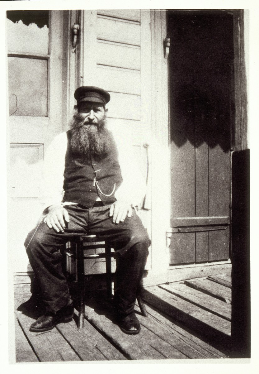 "Reb Dovid ""der Kichier"" Moszczenik sits on the porch in front of his house on Mill Street.   Reb Dovid, controlled and distributed all of the funds sent by the Detroit branch of the Eishyshker society from the late 1920s until his death in the '30s."