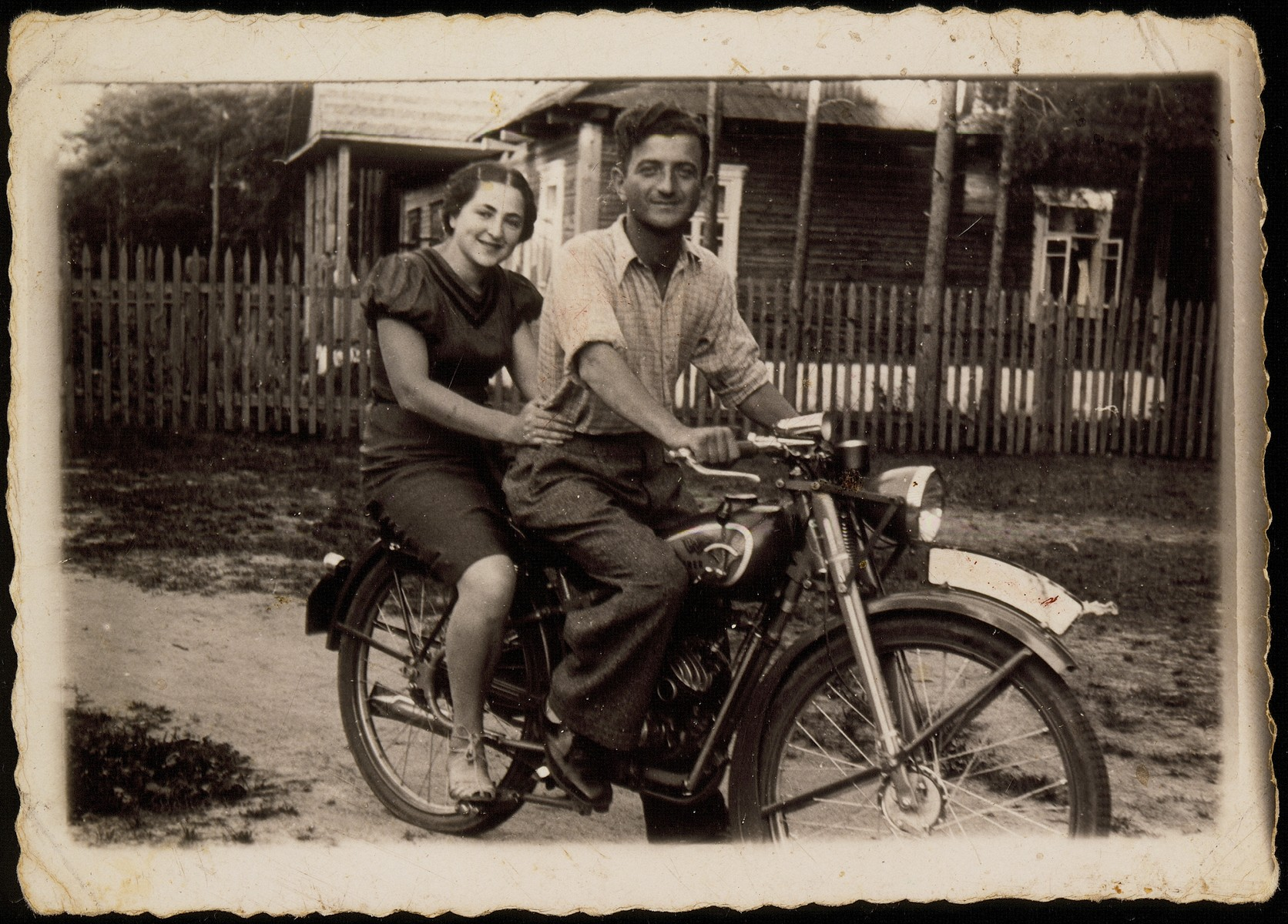 Shabbtai (Shepske) Sonenson takes one of the shtetl's Hebrew teachers for a ride on his new motorcycle.