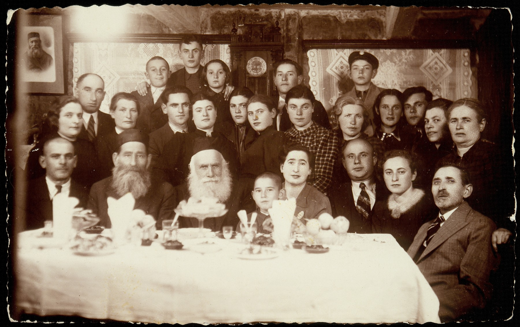 Relatives and friends gather to celebrate the wedding of Sarah Plotnik and Pessah Avrahami; it was one of the last weddings in Eisiskes.  Seated at the table from right to left are Mr. Hamarski, Dvorah Hamarski, Benyamin Kabacznik, Liebke Kabacznik, Yudaleh Kabacznik, Reb Arieh-Leib Kudlanski, Reb Dovid Moszczenik, and the father of the bride, Eliyahu Plotnik. Second row (right to left): Mrs. Hamarski, five family members; twin sisters of the bride, Mikhele and Breine Plotnik, the bride and groom; Zipporah Plotnick, mother of the bride; and two unidentified relatives.    The bride and groom immigrated to Palestine.  Reb Dovid Moszczenik died a natural death.  All the others perished.  Benyamin, Liebke and Yudaleh were murdered by members of the Polish Home Army; the majority were killed in the September 1941 mass killing action in Eisiskes; a few were killed in the Radun and Lida ghettos.