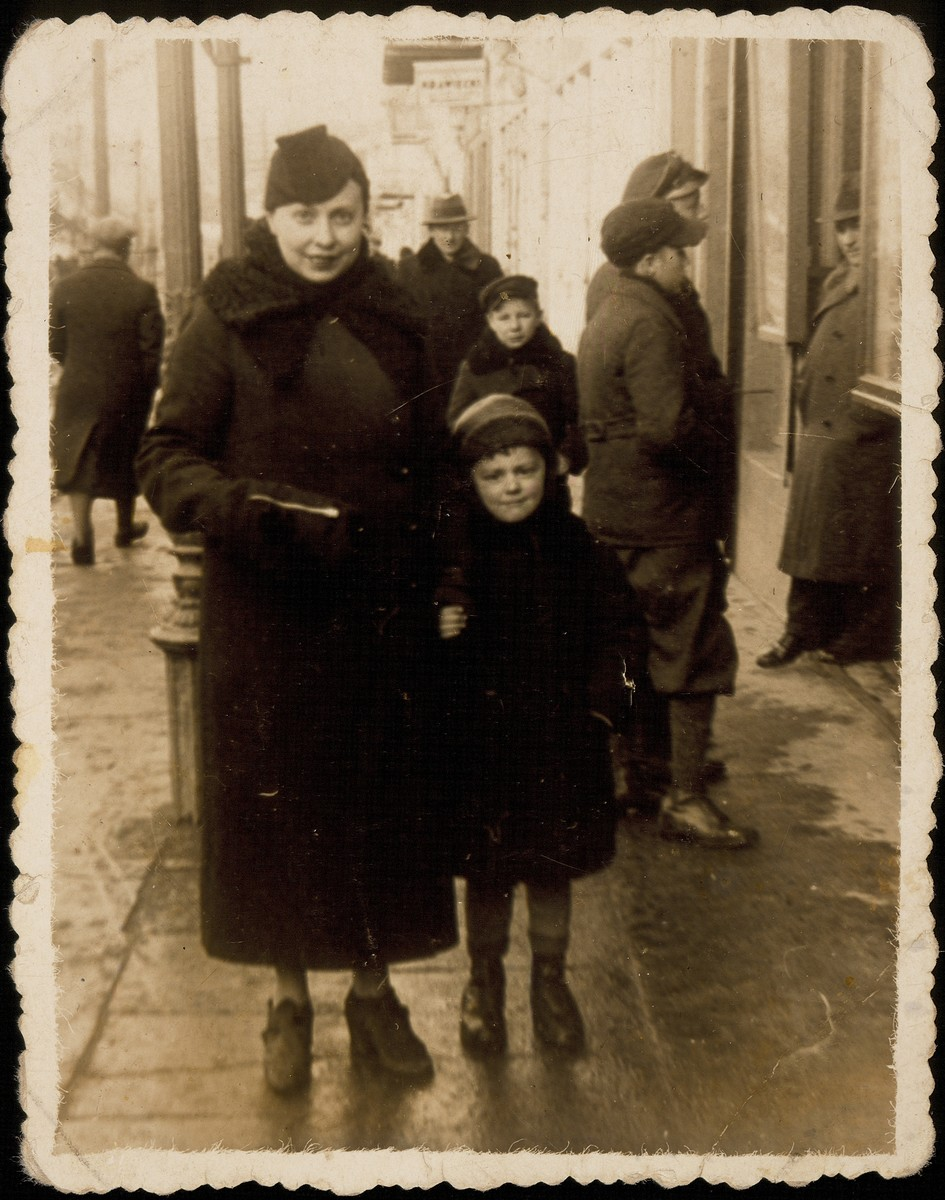 Ida Sonenson walks  down a street in a commercial district with her son Mulka (Meir) during the late 1930s.  Both were killed by the Germans during the September 1941 mass shooting action in Eisiskes.