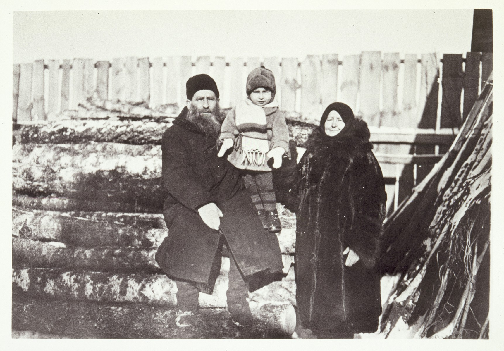 Reb Dovid and Leah Moszczenik pose by a wood pile with their grandson Yudaleh Kabacznik in the family's backyard.   Yudaleh was killed by the Polish Home Army in 1944. Leah was killed by the Germans during the September 1941 mass shooting action in Eisiskes.  Reb Dovid died a natural death.