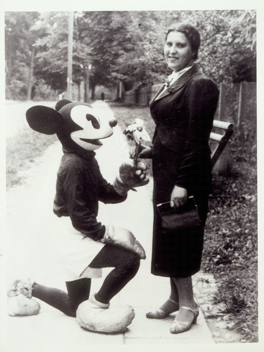Esther Lapp poses with a person dressed as Mickey Mouse in Eisiskes.  Esther Lapp and her family, who were from the town of Olkenik, were killed by the Germans during the September 1941 mass shooting action in Eisiskes.