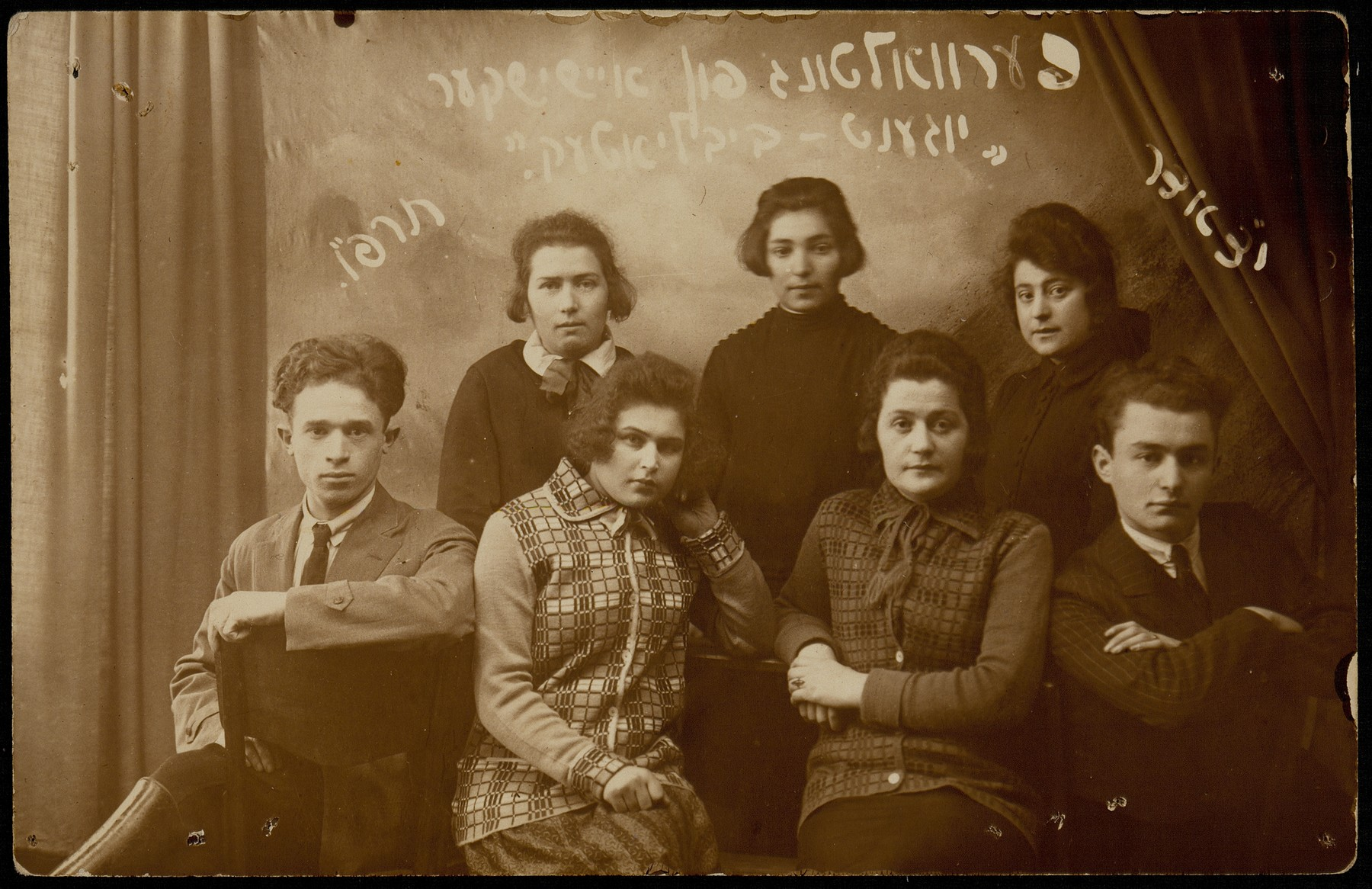 "The Young Library Society in Eisiskes.   Standing from right to left: Feigele (Fanichke) Saltz, Ettl Glombocki, Bat-Sheva Rozowski.  Sitting right to left: Peretz Kaleko, Hannah Koppelman, Shoshana (Shoshke) Yurkanski, unknown. The photo was inscribed in Yiddish, "" To my dear loving sister from Hanka.  1926.""    Feigele (Fanichke) Saltz immigrated to the United States, and Peretz Kaleko immigrated to Palestine.  Ettl Glombocki Gunzberg survived the Holocaust in the Soviet Union.  Shoshana (Shoshke) was murdered by a Russian partisan.  Bat-Sheva Rozowski was mudered in Treblinka.  Hannah Koppelman also perished during the Holocaust."