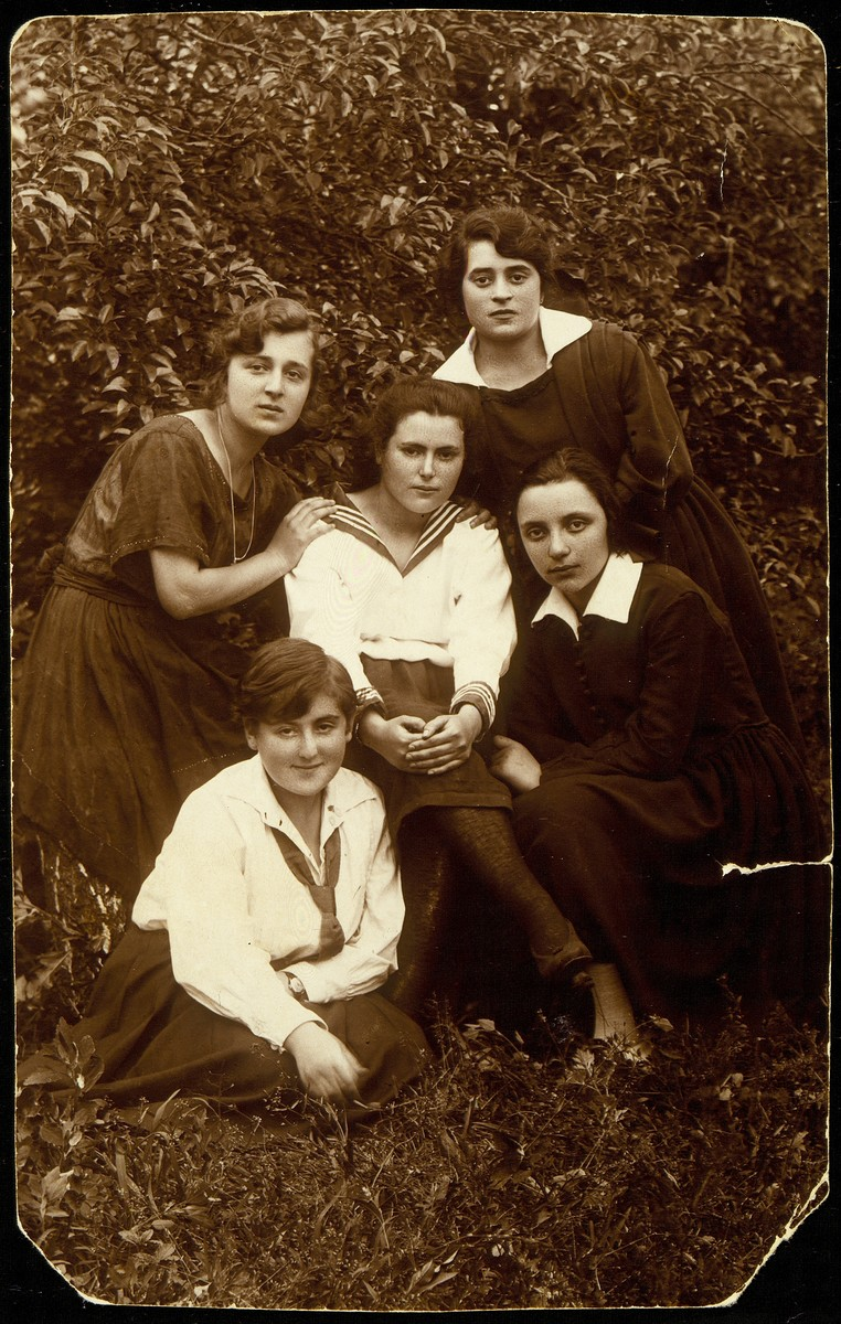Dora Zlotnik Berkowitch sits in a garden with a group of friends from Olkenik.  Dora is pictured in the center row on the far left.  Dora immigrated to Palestine.  The fate of the other women is unknown.
