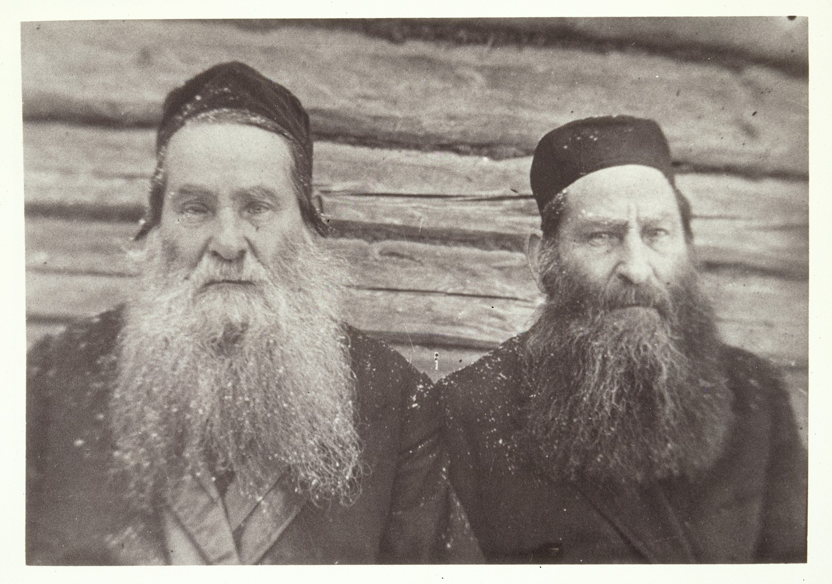 """Portrait of the two Moszczenik brothers    (Right to left), Reb Dovid """"der Kichier"""" and """"Reb Zvi-Hersh the Garden Preacher.""""  He earned his nickname since he spoke to his vegetable garden every day.  He was also known as the """"Reb Zvi-Hersh the Hafetz Hayyim's Preacher"""", since he raised funds for his Yeshivah.  The inscription on the back of the photo reads: """"We were photographed in the backyard of Liebke while a snow was falling."""""""
