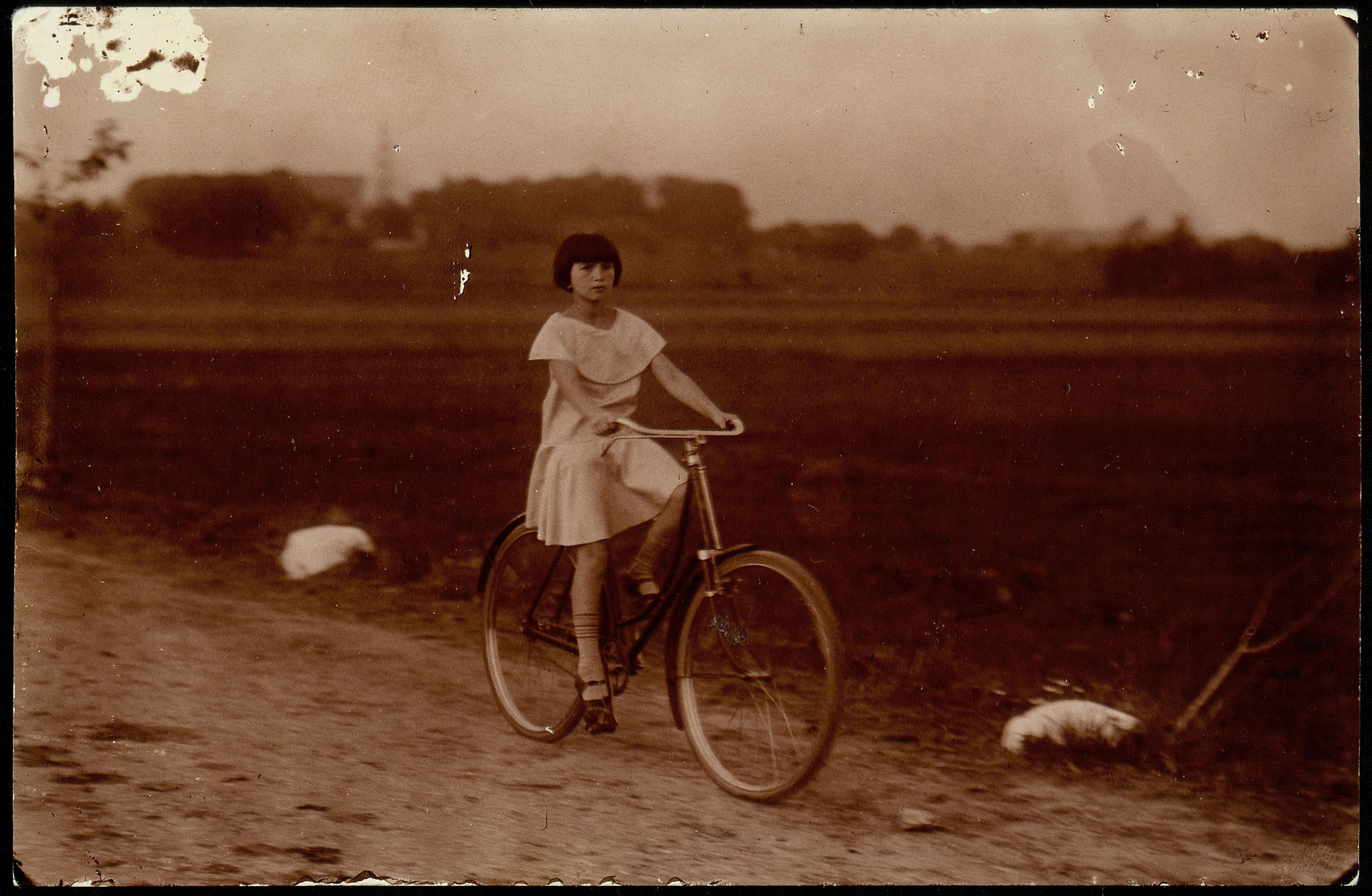 Atara Kudlanski rides a rented bicycle down a dirt road on the outskirts of Eisiskes.   Her dress was a gift from her Aunt Sara in America.  In 1933 Atara joined her father in the United States.