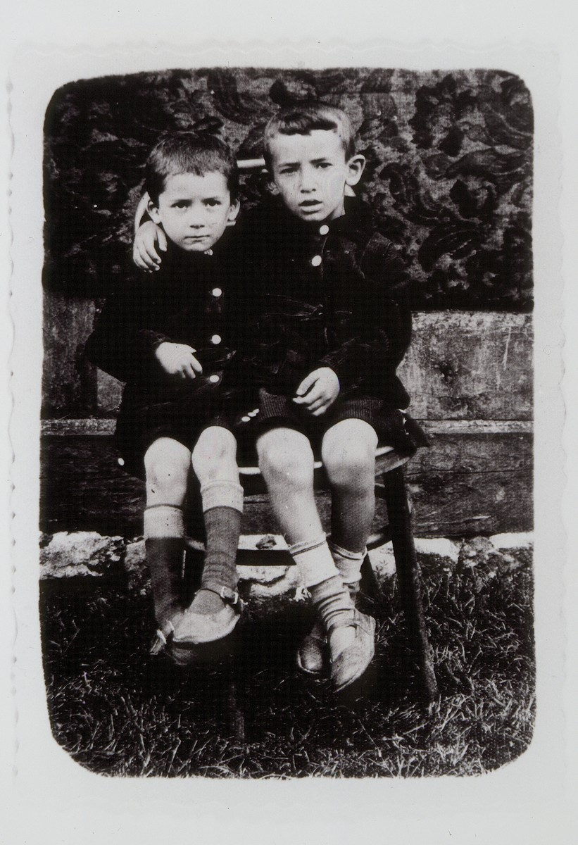 Two young boys share a chair.