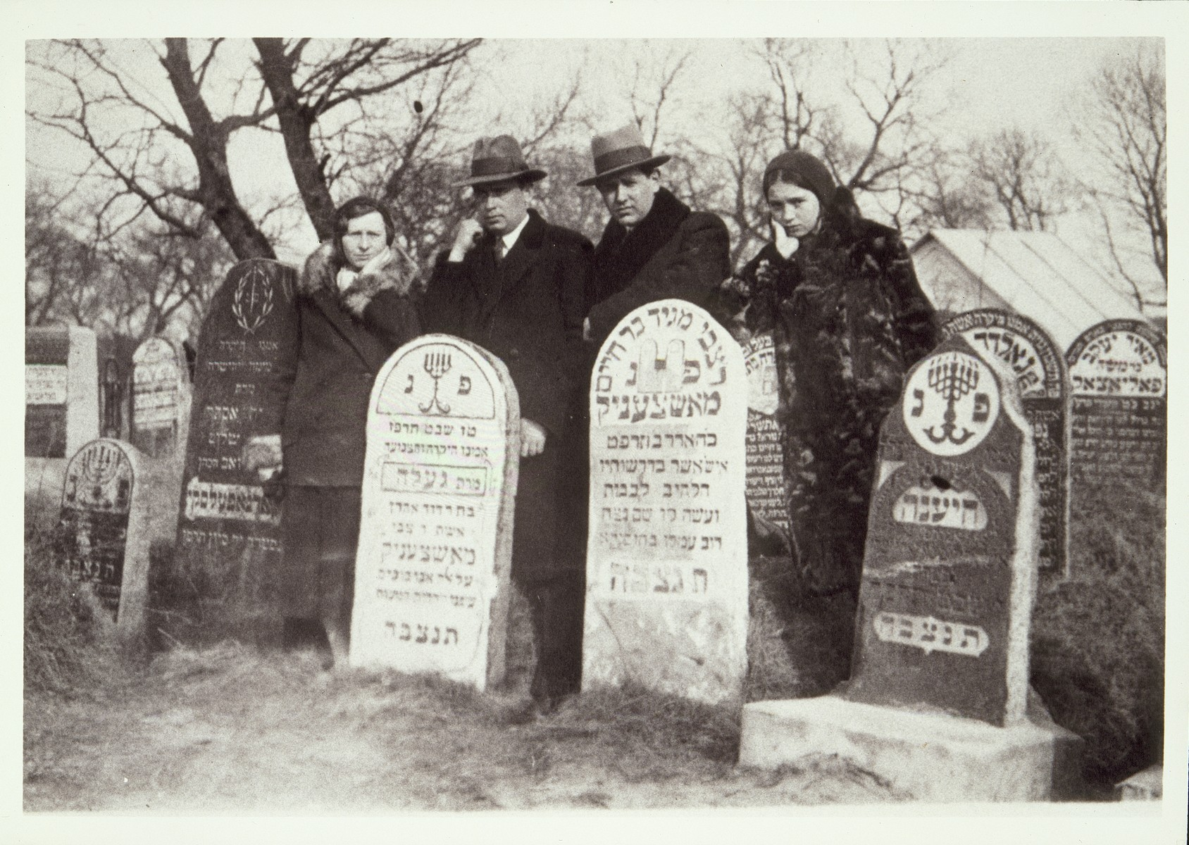 """Hanneh-Beile Kudlanski (left), her daughter Atara (right) and other family members bid farewell to departed ancestors before immigrating to  America.   On the right is the tombstone of Hanneh-Beile's uncle Reb Zvi Hersh Moszczenik, """"the  Garden Preacher""""; on the left is the tombstone of his wife Gelle."""