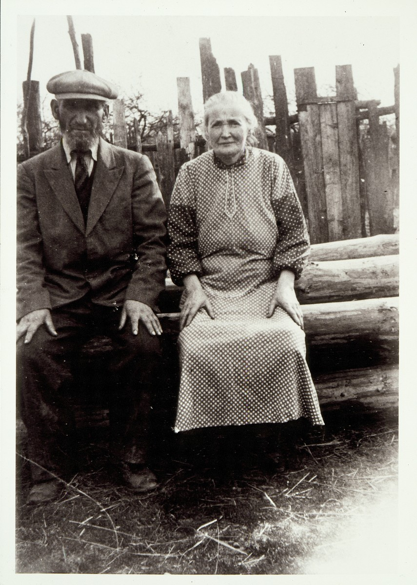 Reuven-Beinush Berkowitch and his wife Rachel Kabacznik sit outdoors on a pile of logs.  Reuven-Beinush married Rachel Kabacznik after the death of his first wife, Golde, Rachel's sister.  Reuven-Beinush and Rachel were both murdered in the September 1941 mass killing action in Eisiskes.