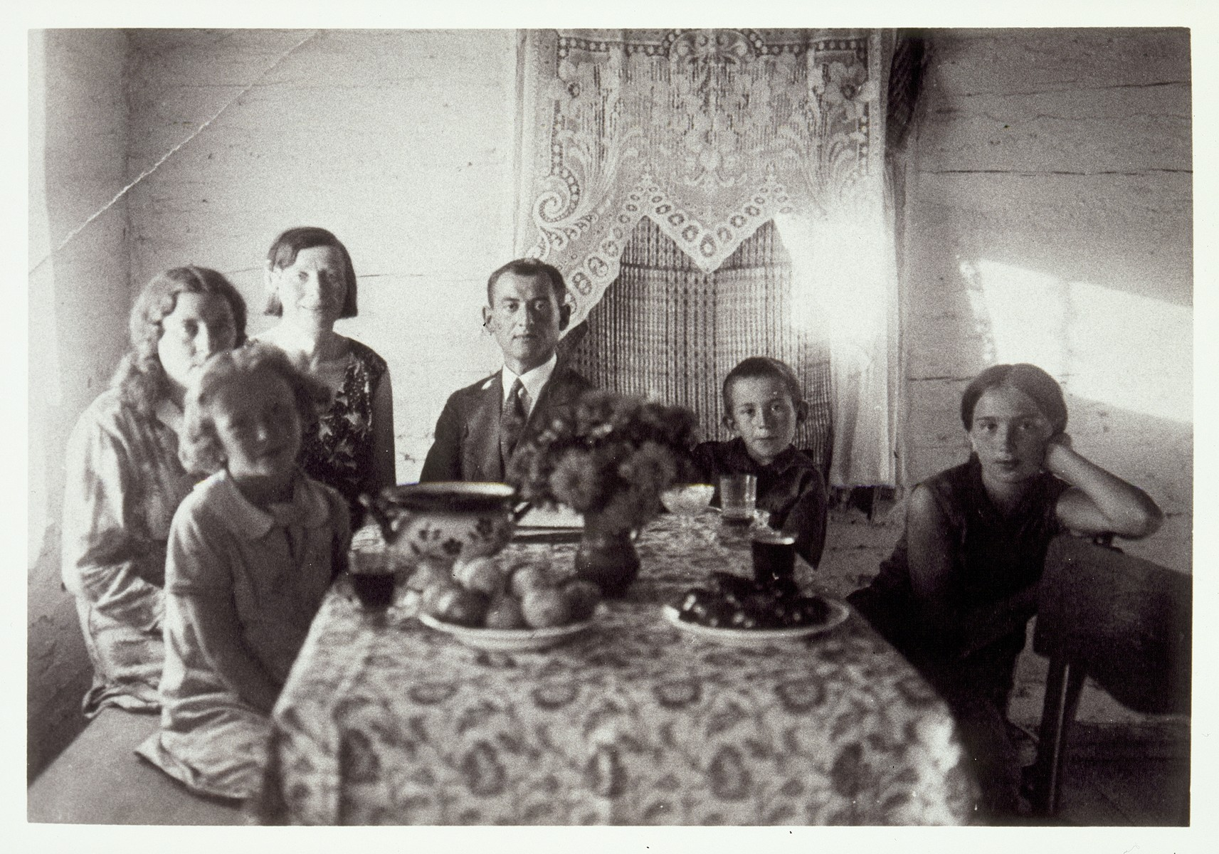 Dr. Zytoner, an assimilated Jewish veterinarian from Warsaw, sits in the center of a group of women and children around the Moszczenik dining room table.   Dr. Zytoner boarded at the Moszczenik home while working in Eisiskes.  Pictured from right to left are Atara Kudlanski, her brother Bill, Dr. Zytoner, Atara and Bill's mother Hanneh-Beile  (nee Moszczenik), her sister Liebke, and her daughter Zltaka.    Hanneh-Beile and her three children immigrated to America.  Liebke was killed by the Polish Home Army.