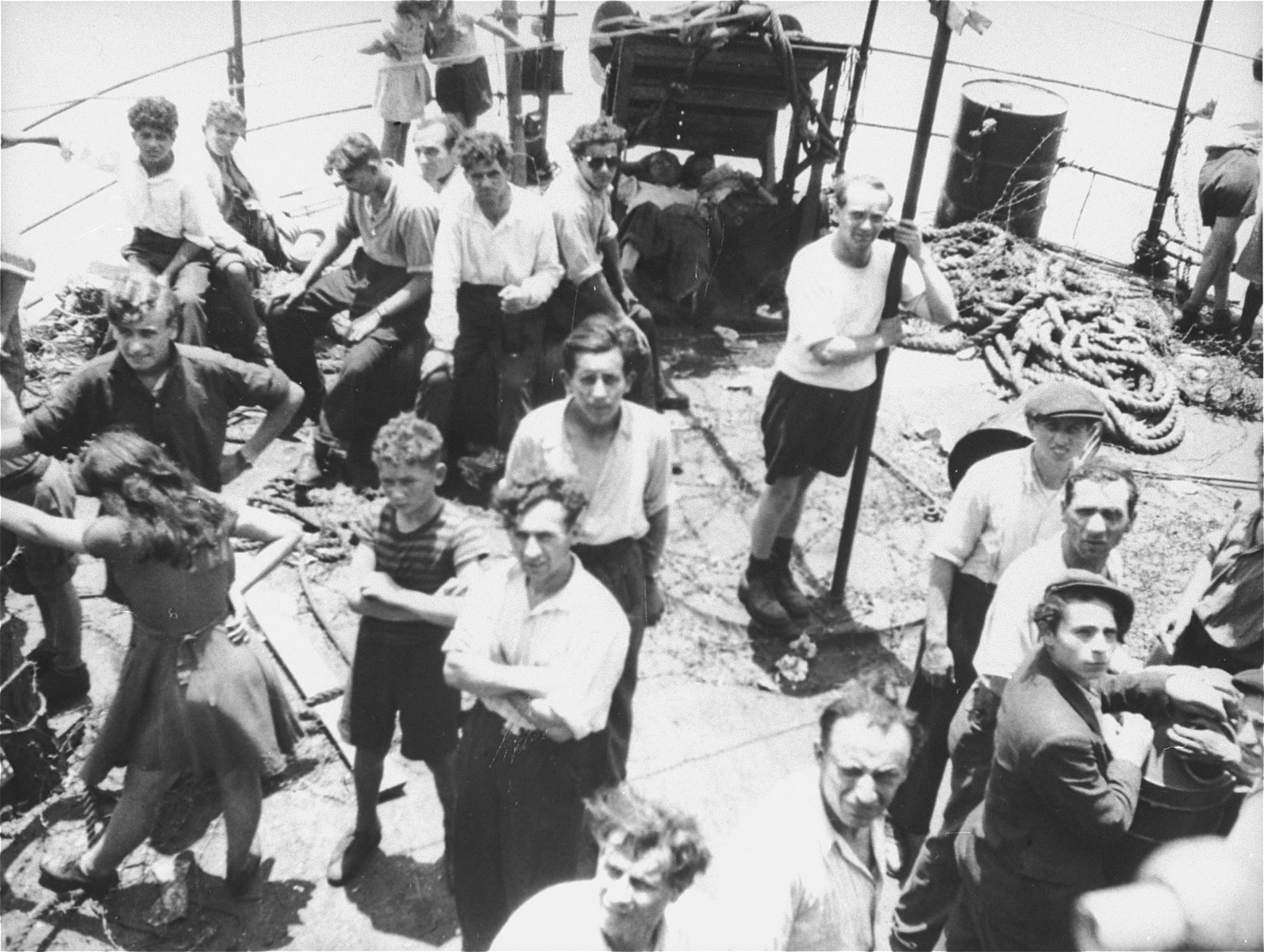 Jewish passengers stand on the deck of the Exodus 1947 amidst the debris from the previous night's struggle.