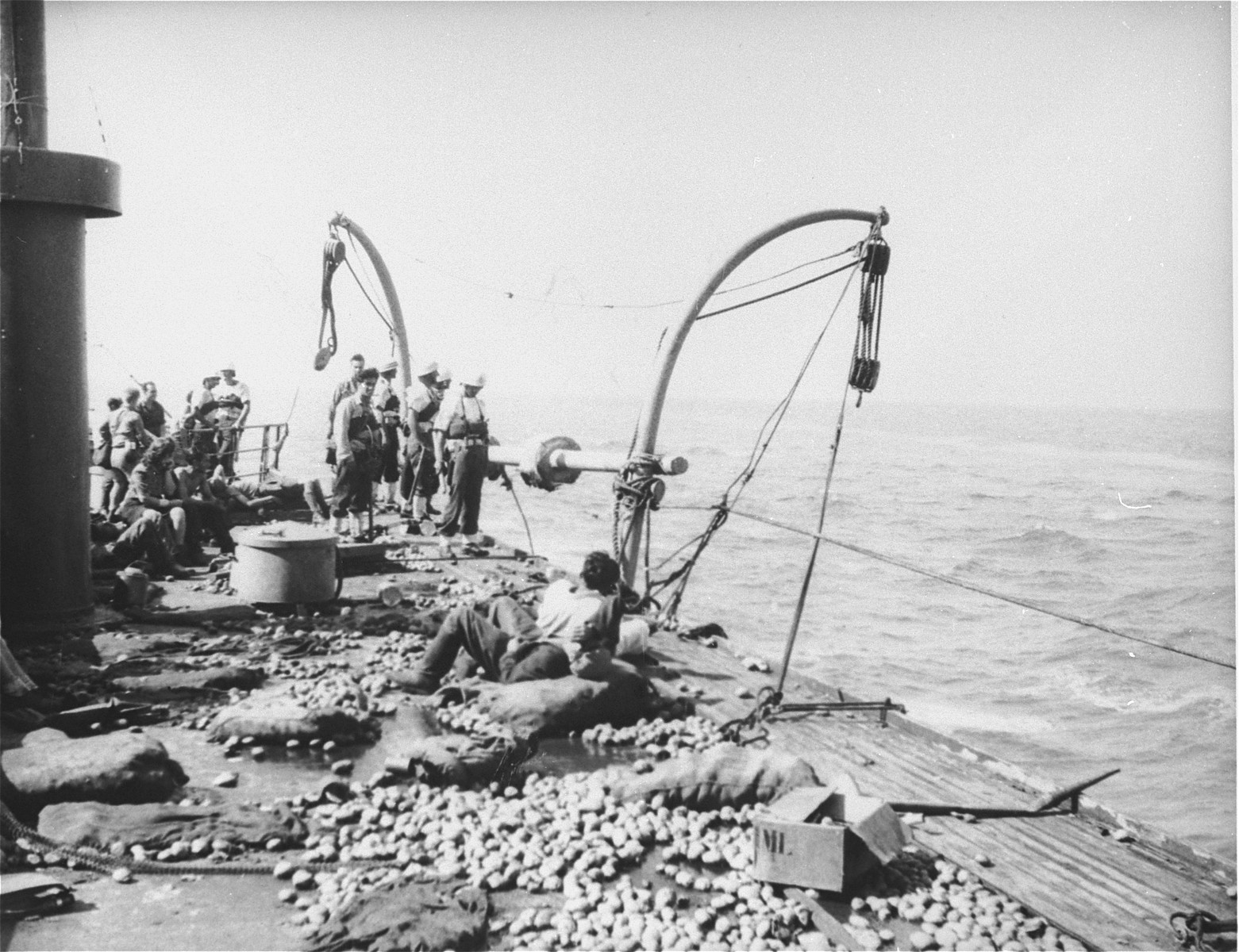 Jewish passengers and British marines stand on the deck of the Exodus 1947 amidst the debris from the previous night's struggle.