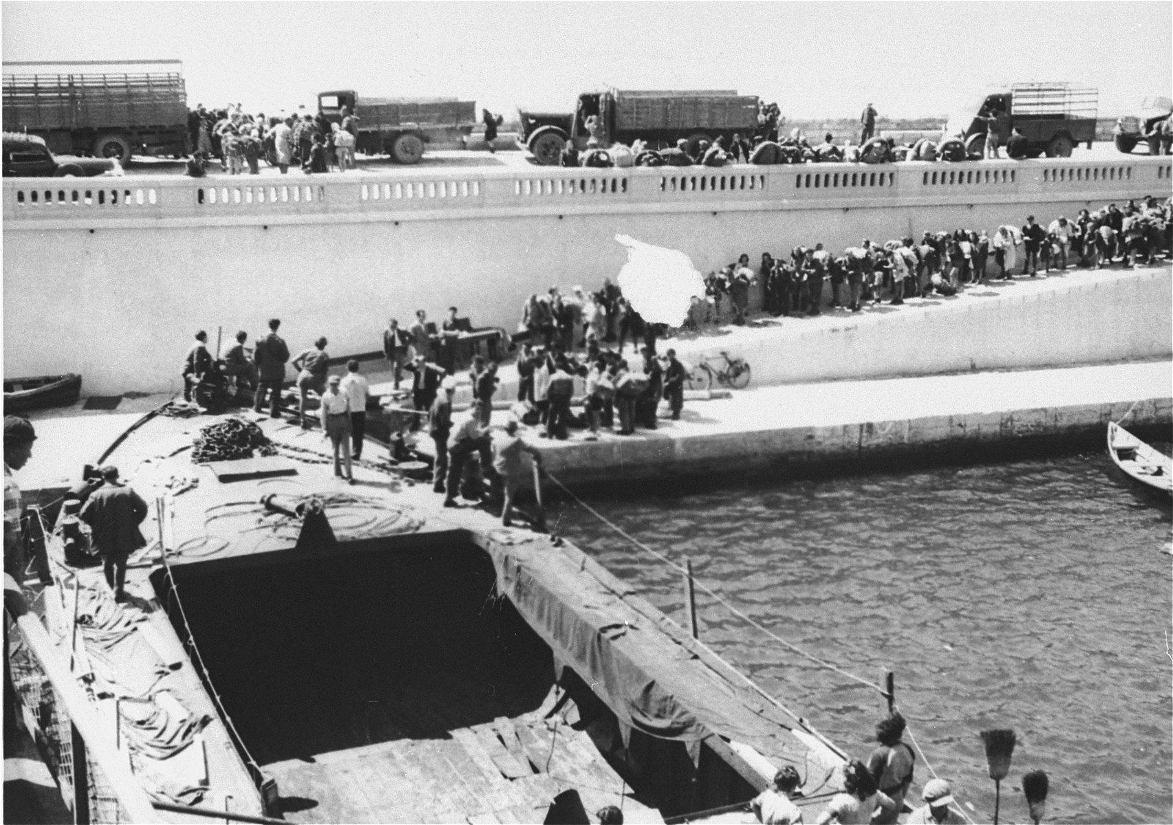 Exodus 1947 refugees make their way along a quay in Sete's harbor toward the President Warfield.