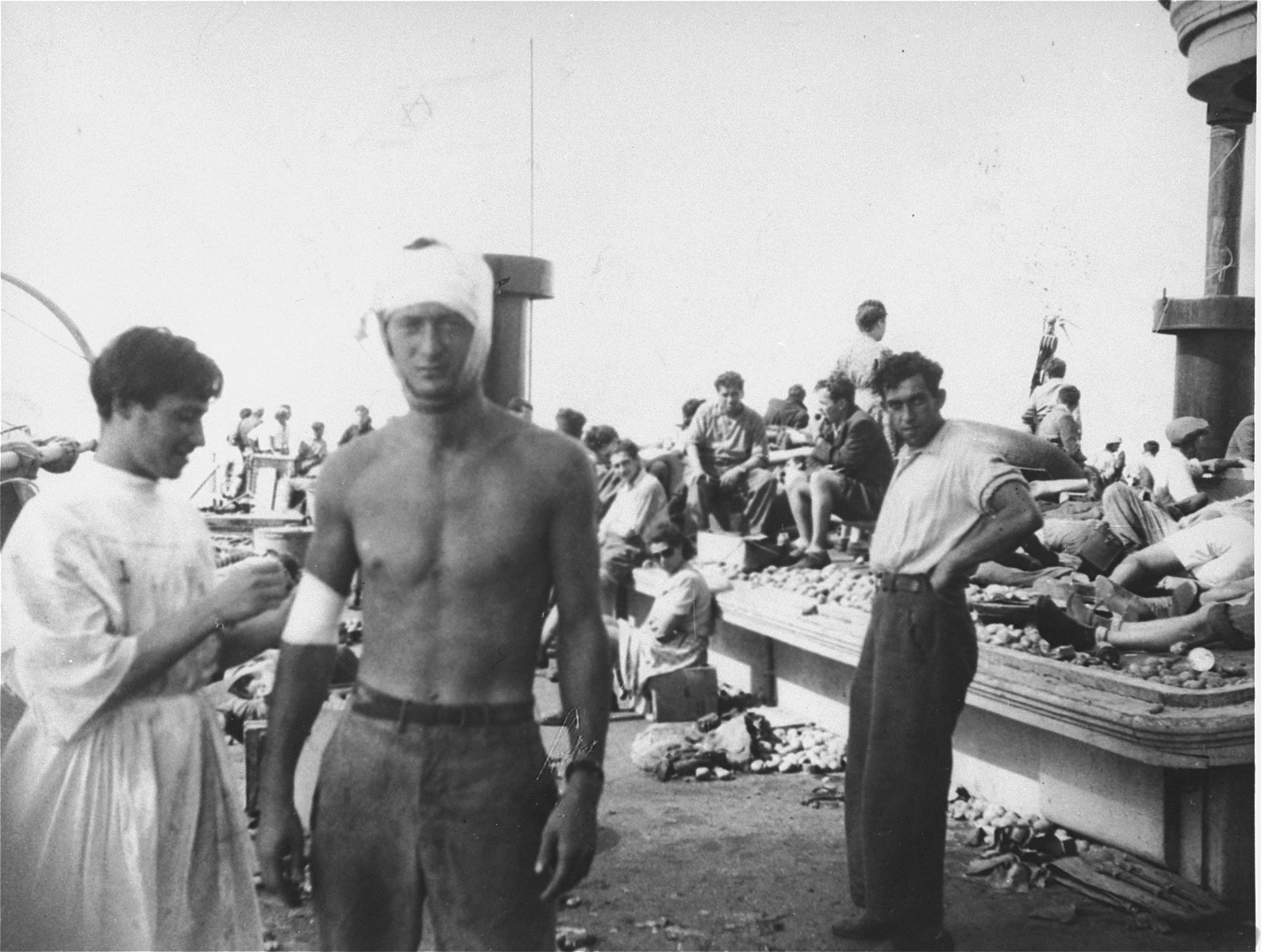On board the damaged Exodus 1947, a medic applies a bandage to crew member Murray Aronoff, who was wounded the night before, during the struggle with the British.