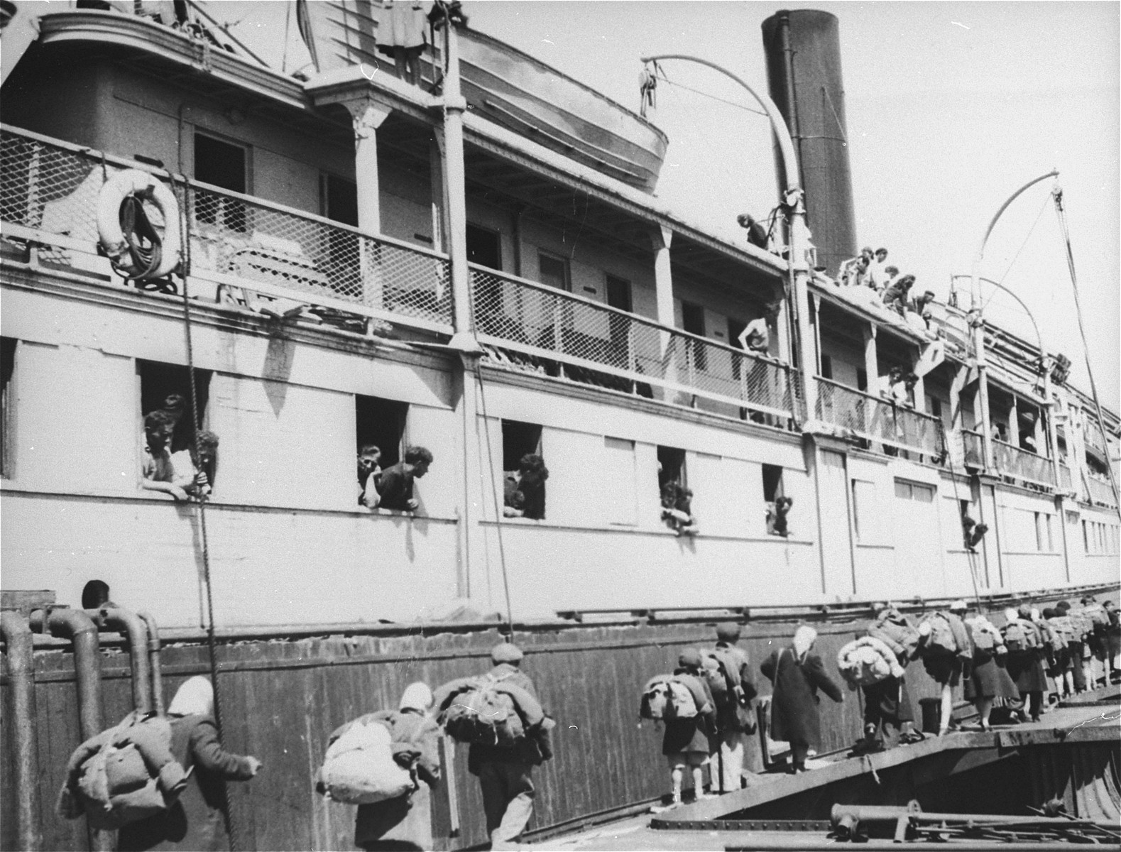Exodus 1947 refugees board the President Warfield, docked at a quay in Sete's harbor, from a neighboring boat.