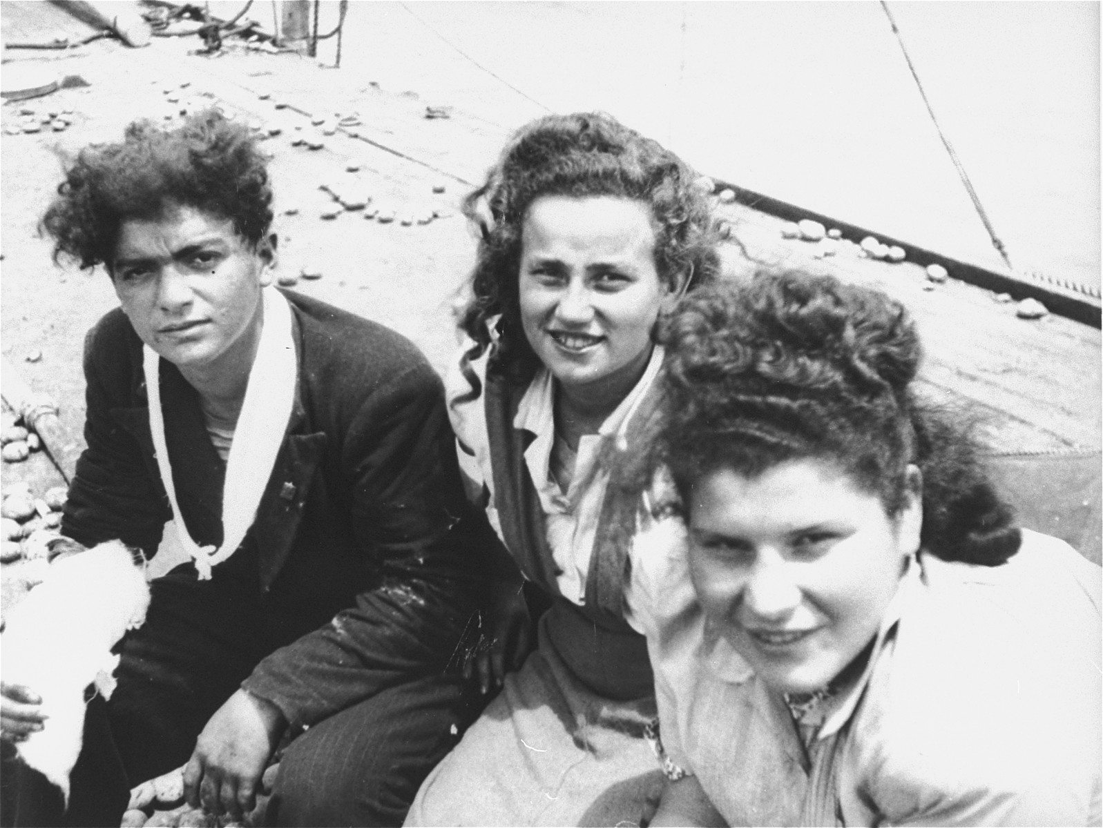 Three Jewish passengers, one of whom has been wounded, sit on the deck of the Exodus 1947.  Potatoes and other debris, used in the struggle with the British, lie on the deck behind them.