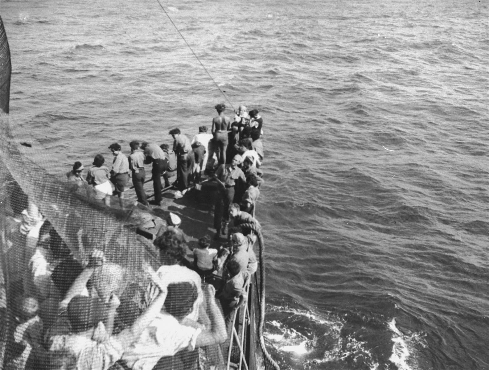 Jewish passengers crowd the bow of the Exodus 1947 as it is towed into the port of Haifa.