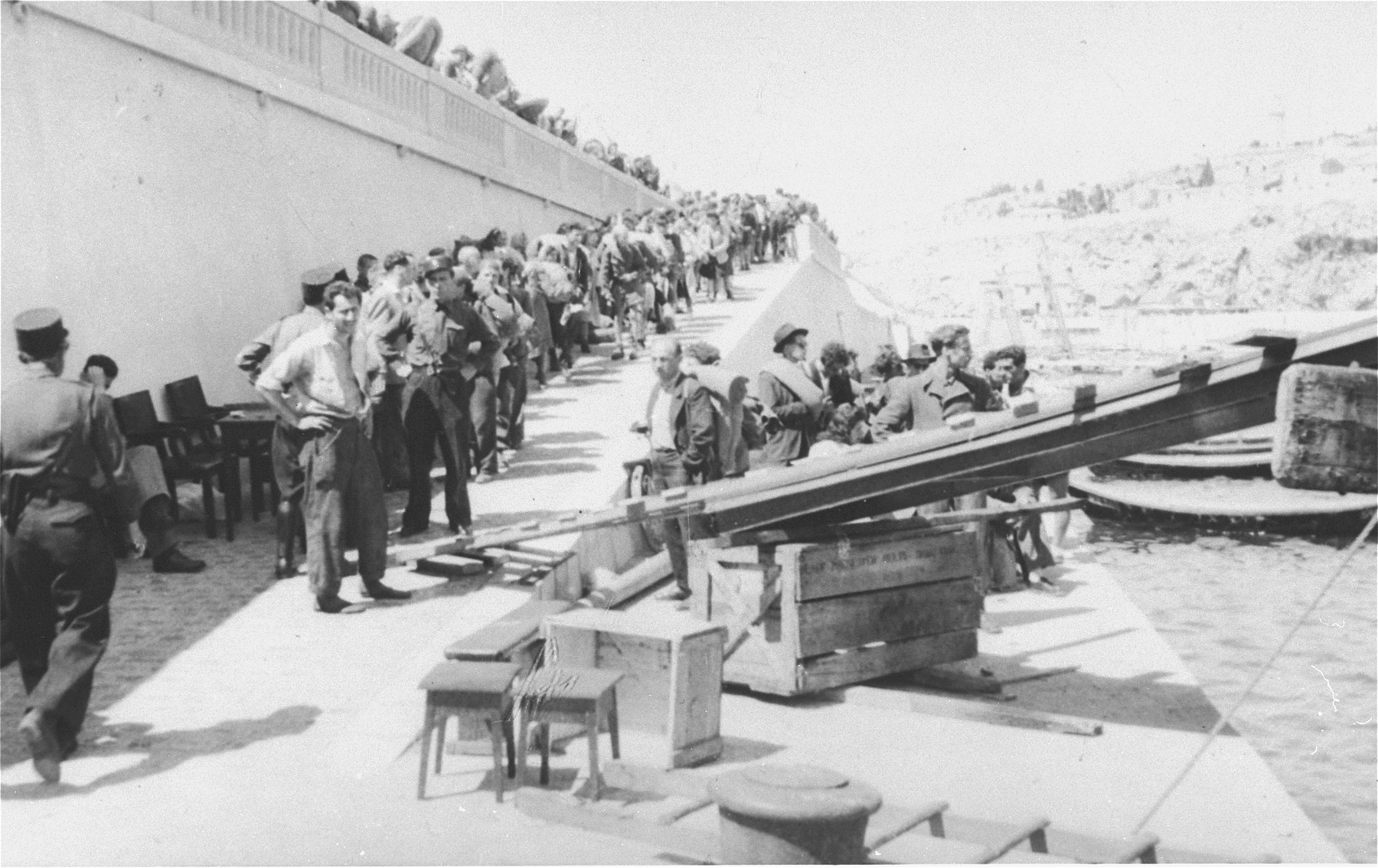 Watched by French policemen, Exodus 1947 refugees board the President Warfield, which is docked at a quay in Sete's harbor.