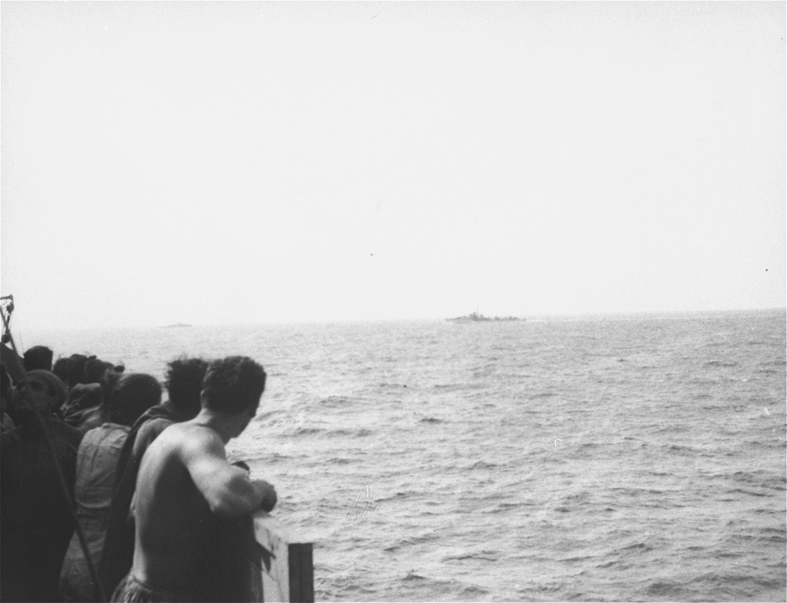 Passengers aboard the Exodus 1947 view the two British warships that have been dispatched to prevent their immigration to Palestine.
